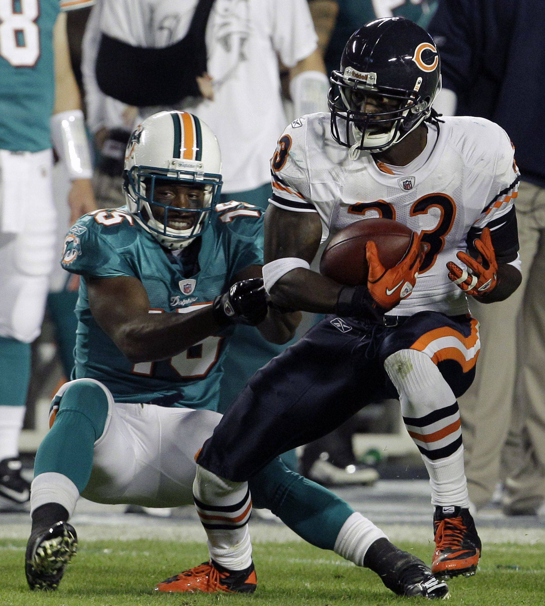 Chicago Bears cornerback Charles Tillman, right, is taken down by Miami Dolphins wide receiver Davone Bess after intercepting a pass during the first quarter.
