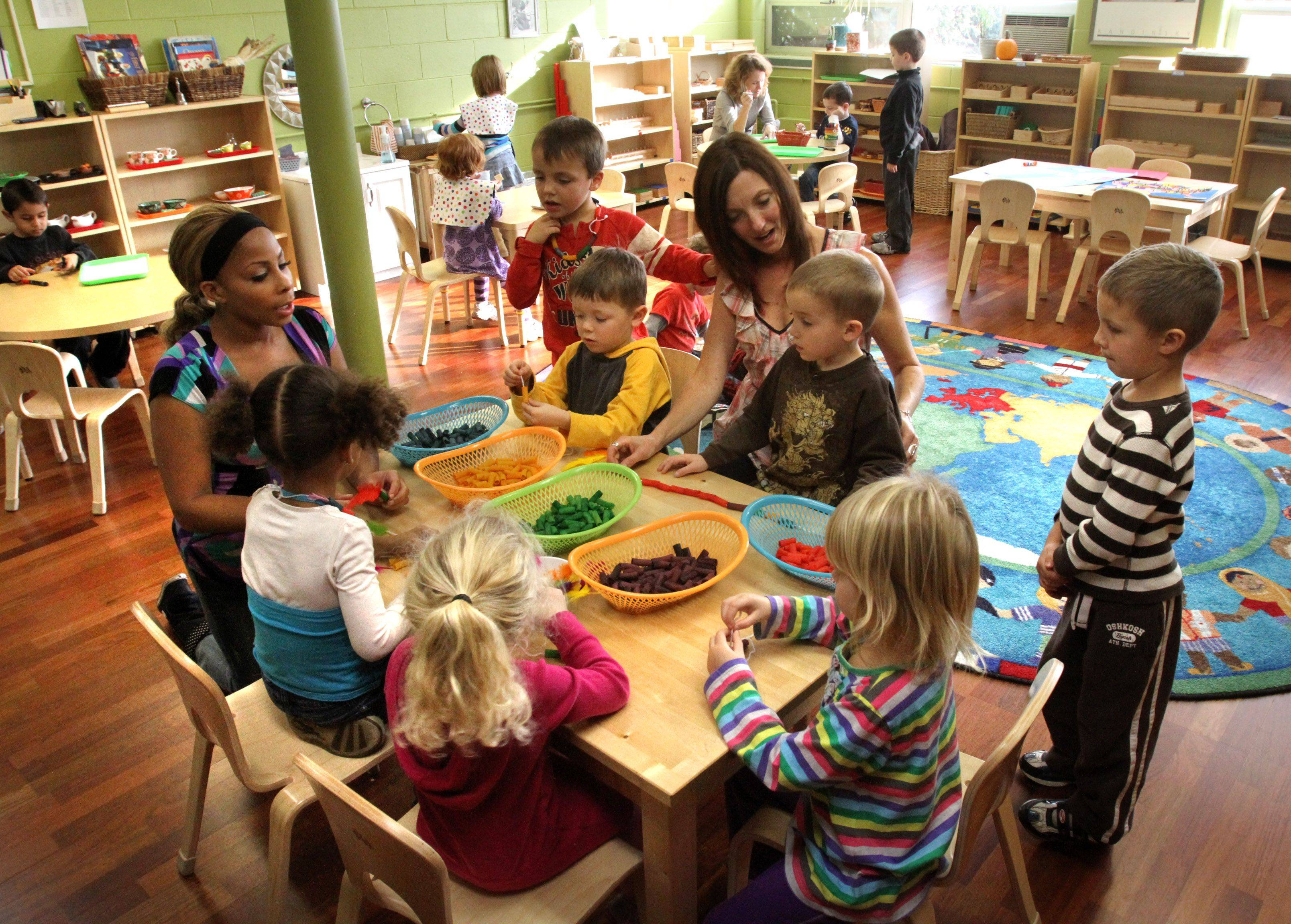 Nicole Shemroske, director of the new Montessori room, center, and assistant teacher Teiama Sippio, left, work with children at Village Green Montessori School at St. Lawrence Episcopal Church in Libertyville.