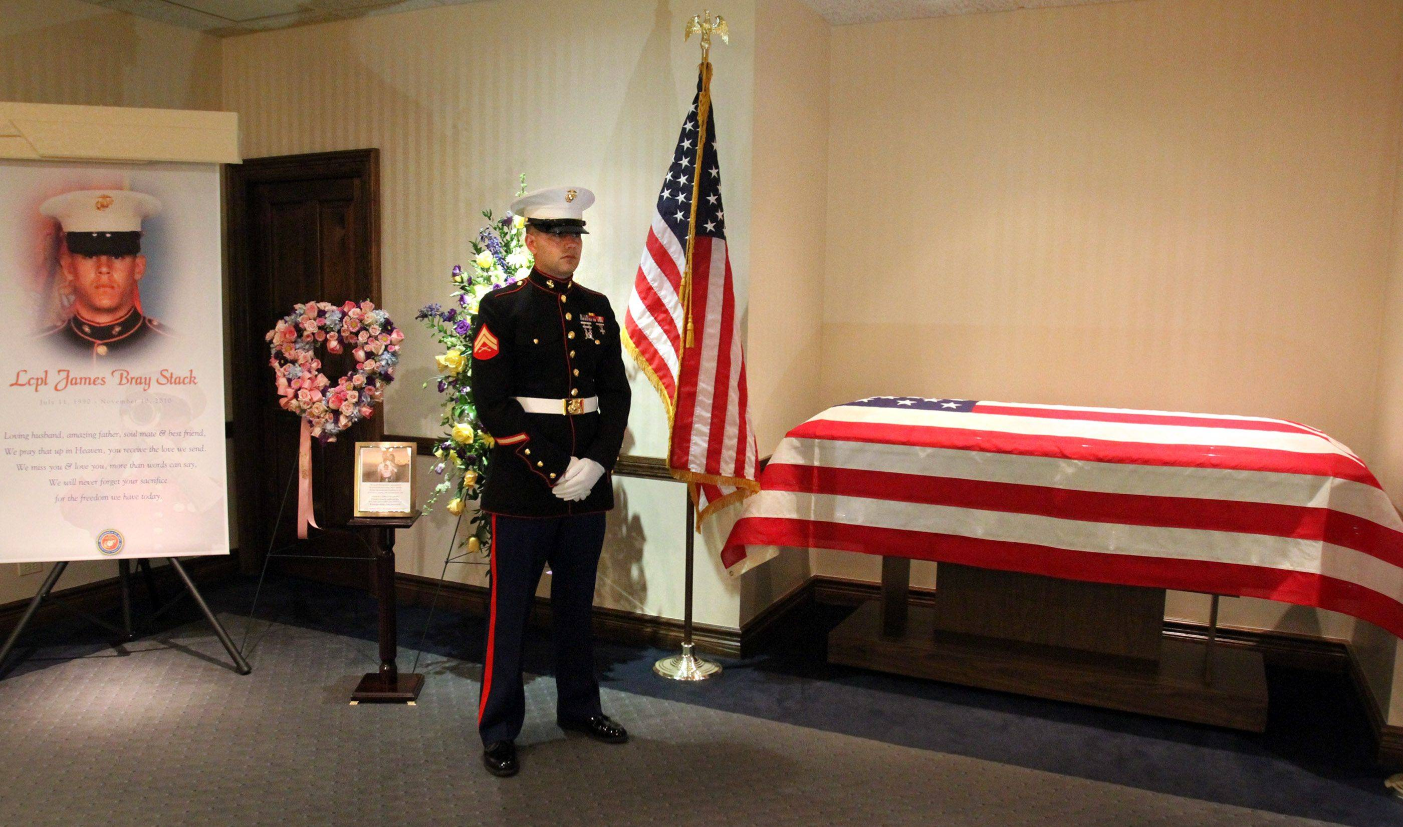 Marine honor guard Cpl. Adam Hermanowicz, with the Marine Air Command Group in Waukegan, guards the flag-draped casket of Lance Cpl. James Stack, before the wake at Glueckert Funeral Home in Arlington Heights.