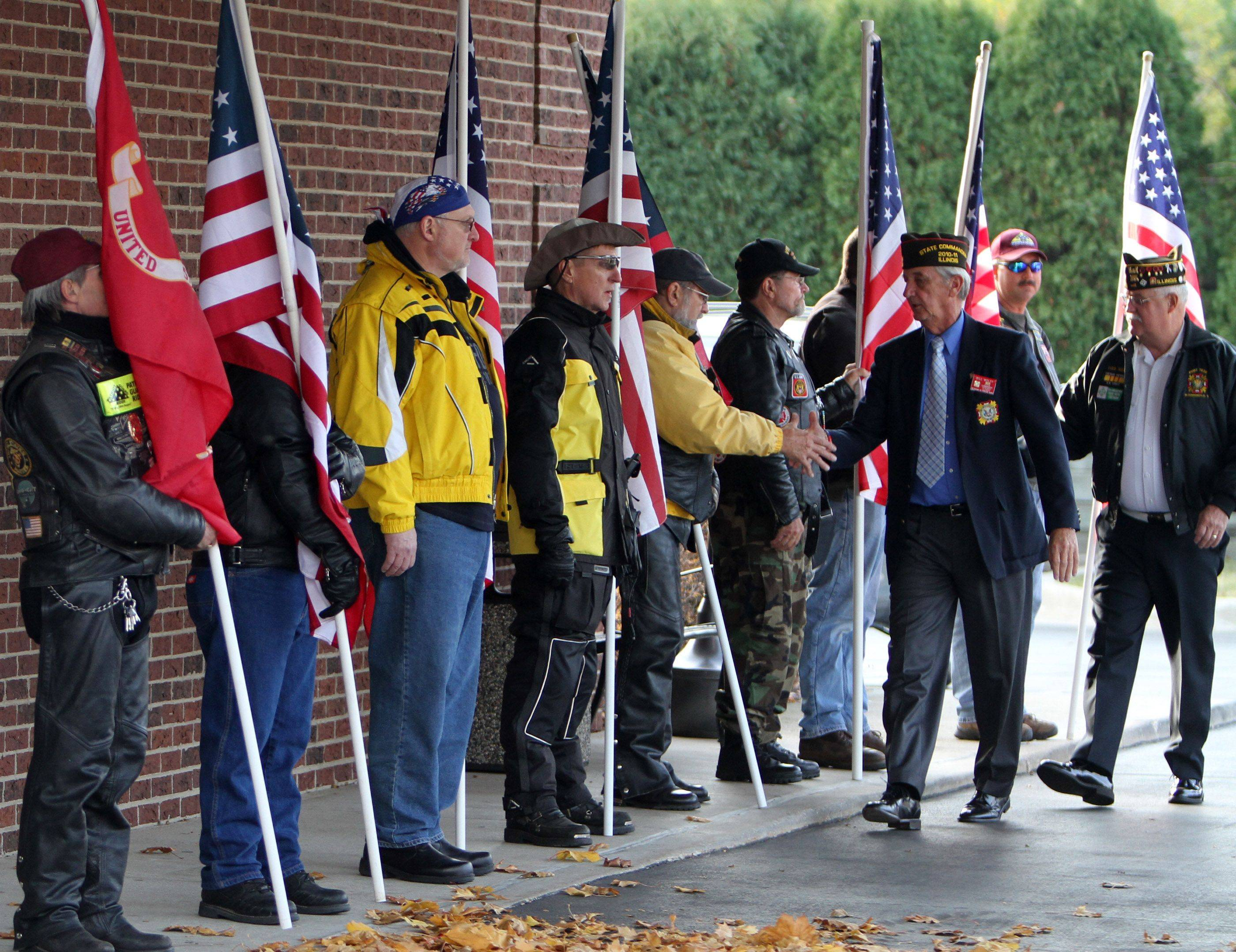 George LeClaire/gleclaire@dailyherald.comIllinois Patriot Guard members stand with an American flag in front of Glueckert Funeral Home, in Arlington Heights, for the wake for Marine Lance Cpl. James Stack, 20, of Arlington Heights Arlington Heights on Friday, November 19th.