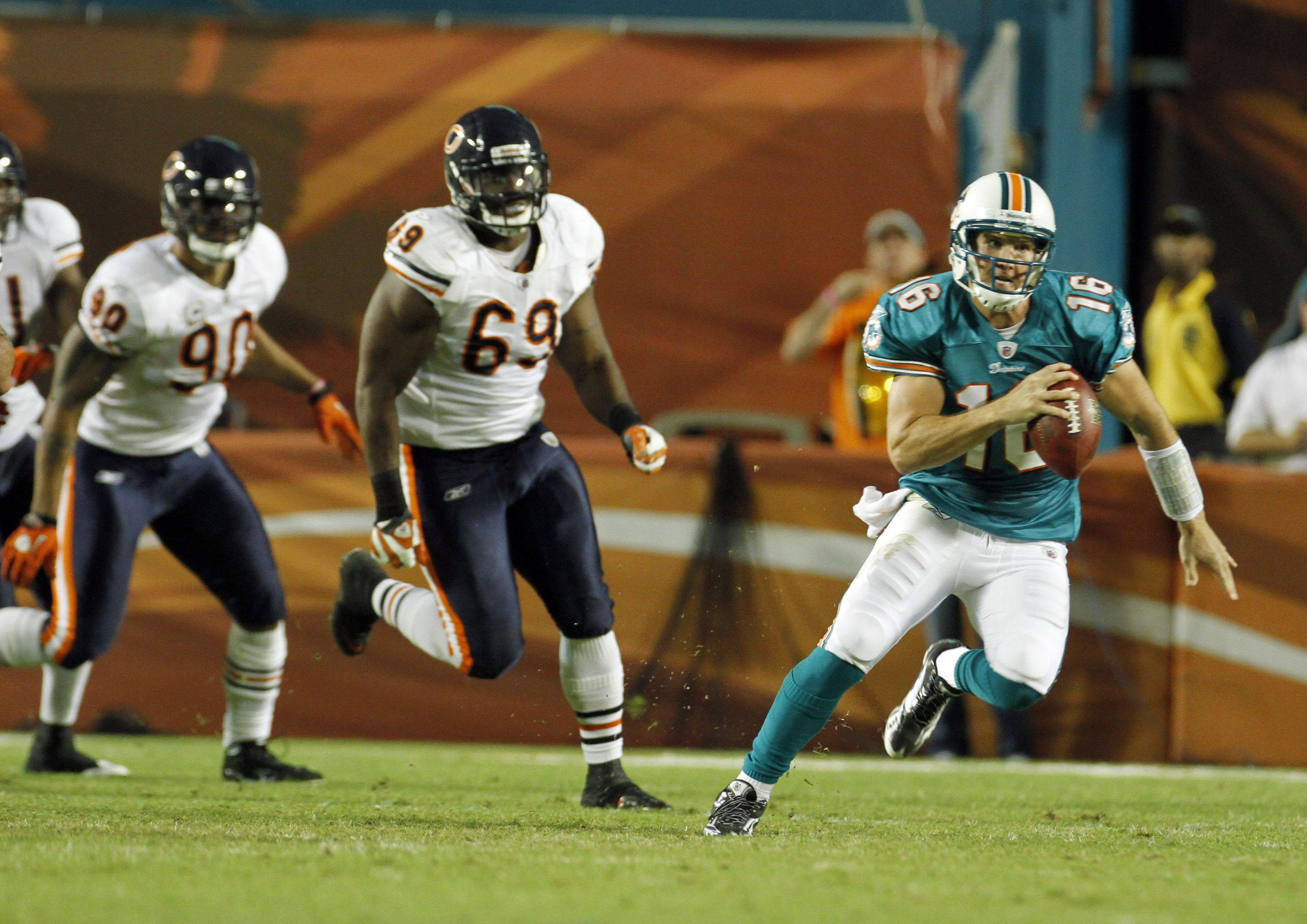 The Bears' Julius Peppers (90) and Henry Melton chase Dolphins quarterback Tyler Thigpen on Thursday. The Bears sacked Thigpen six times.