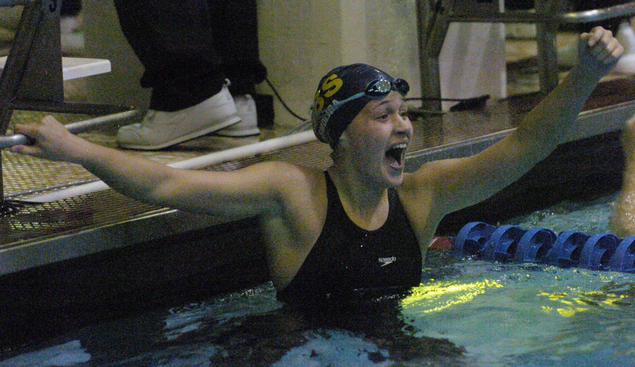 Olivia Smoliga of Glenbrook South celebrates after breaking the state record in the 100-yard back stroke during Friday's girls state swimming prelims at Evanston High School.