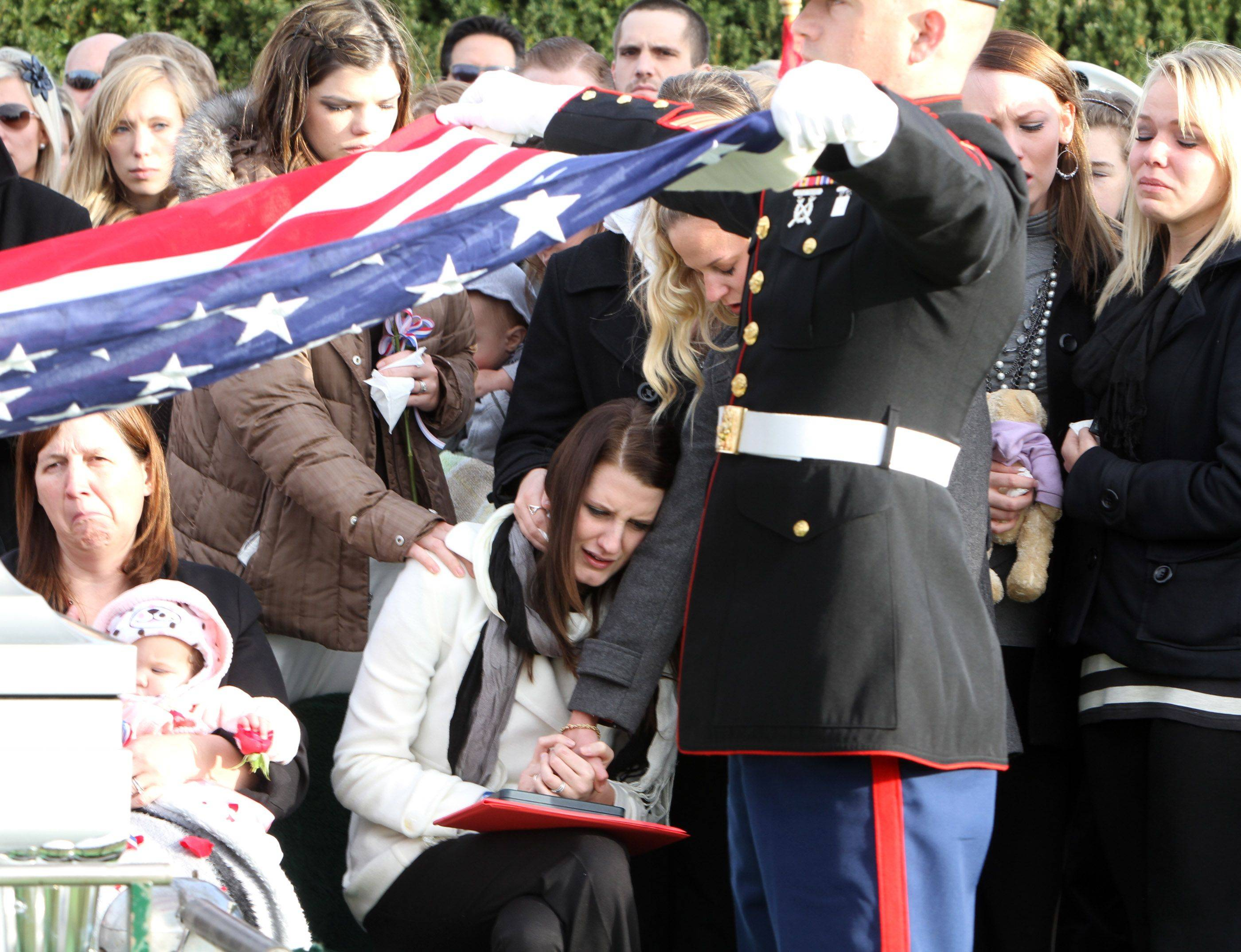 Katie Stack, lower center right, holds the hand of a friend as Marines fold the flag that draped her husband's casket at Memory Gardens Cemetery in Arlington Heights.