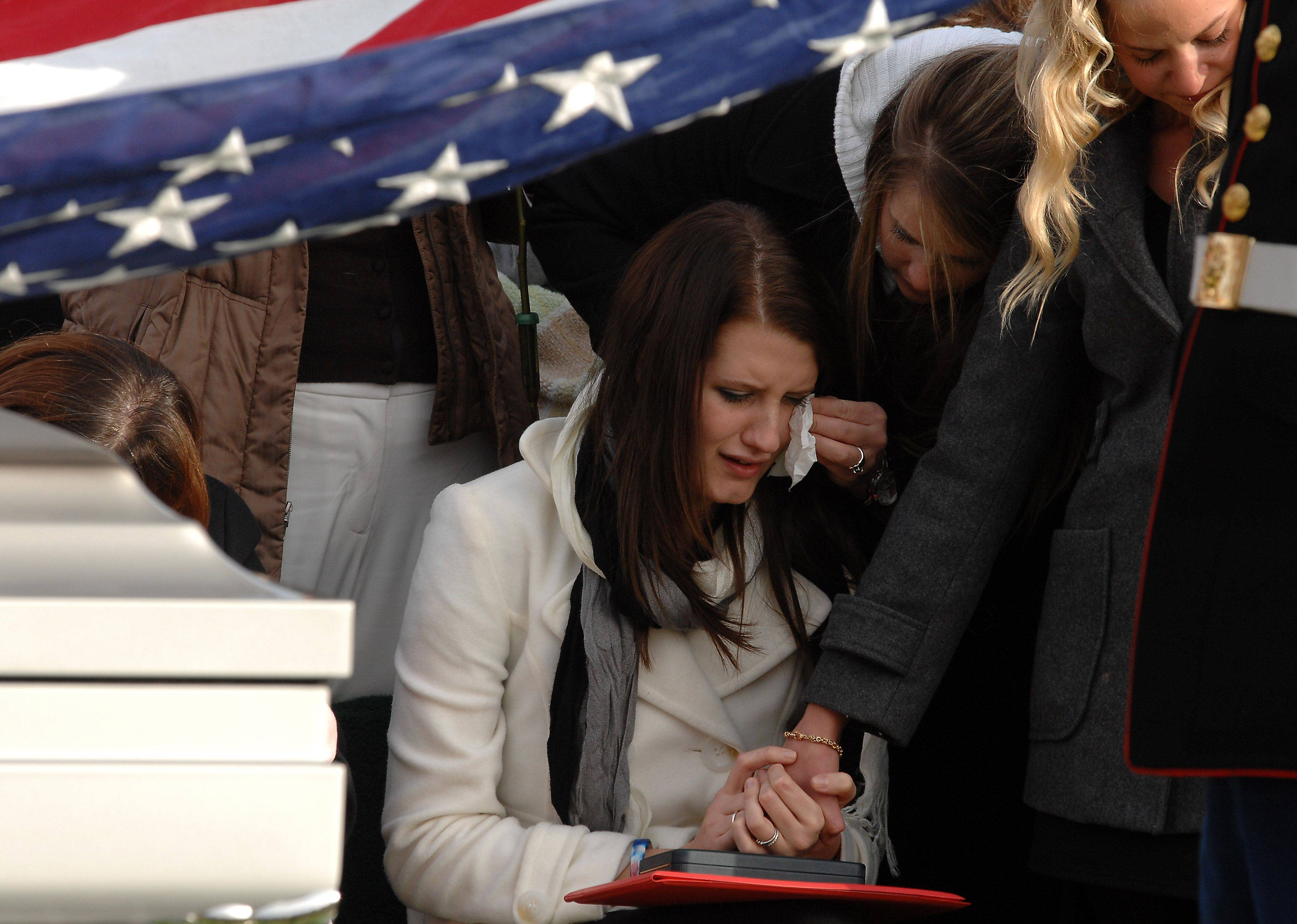 Katie Stack, wife of Lance Cpl. James Stack, wipes away tears as the flag is removed from her husband's casket Saturday at Memory Gardens in Arlington Heights.
