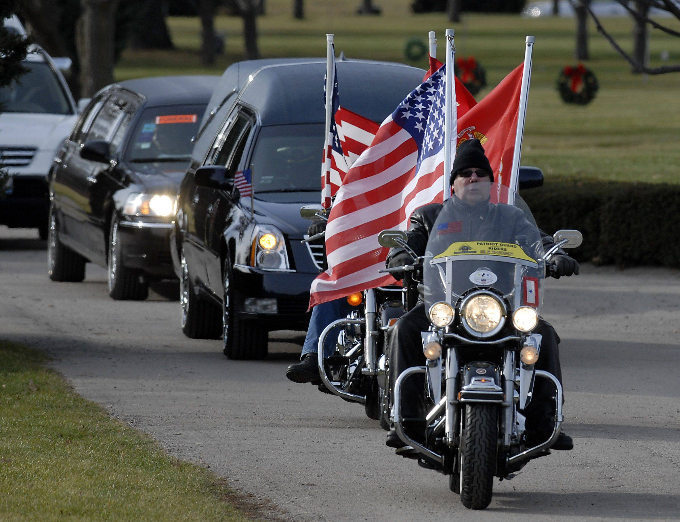 The Patriot Guard leads the hearse and family into Memory Gardens in Arlington Heights for the funeral of Lance Corporal James Stack.