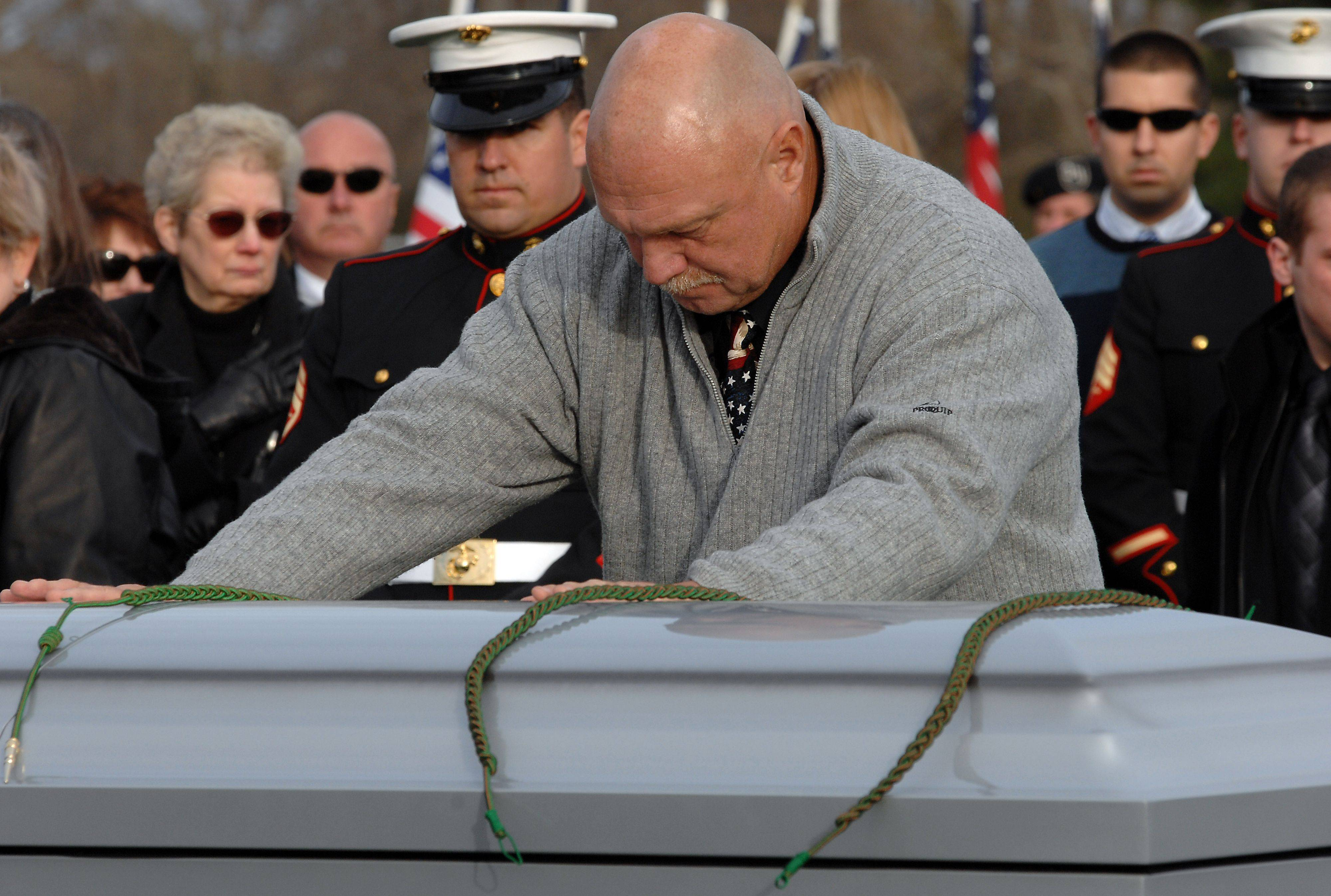Dean Schulatz of Itasca who is a cousin to the family lays his hands on the coffin of Lance Corporal James Stack in a final goodbye after the funeral service in Memoral Garden on Saturday.