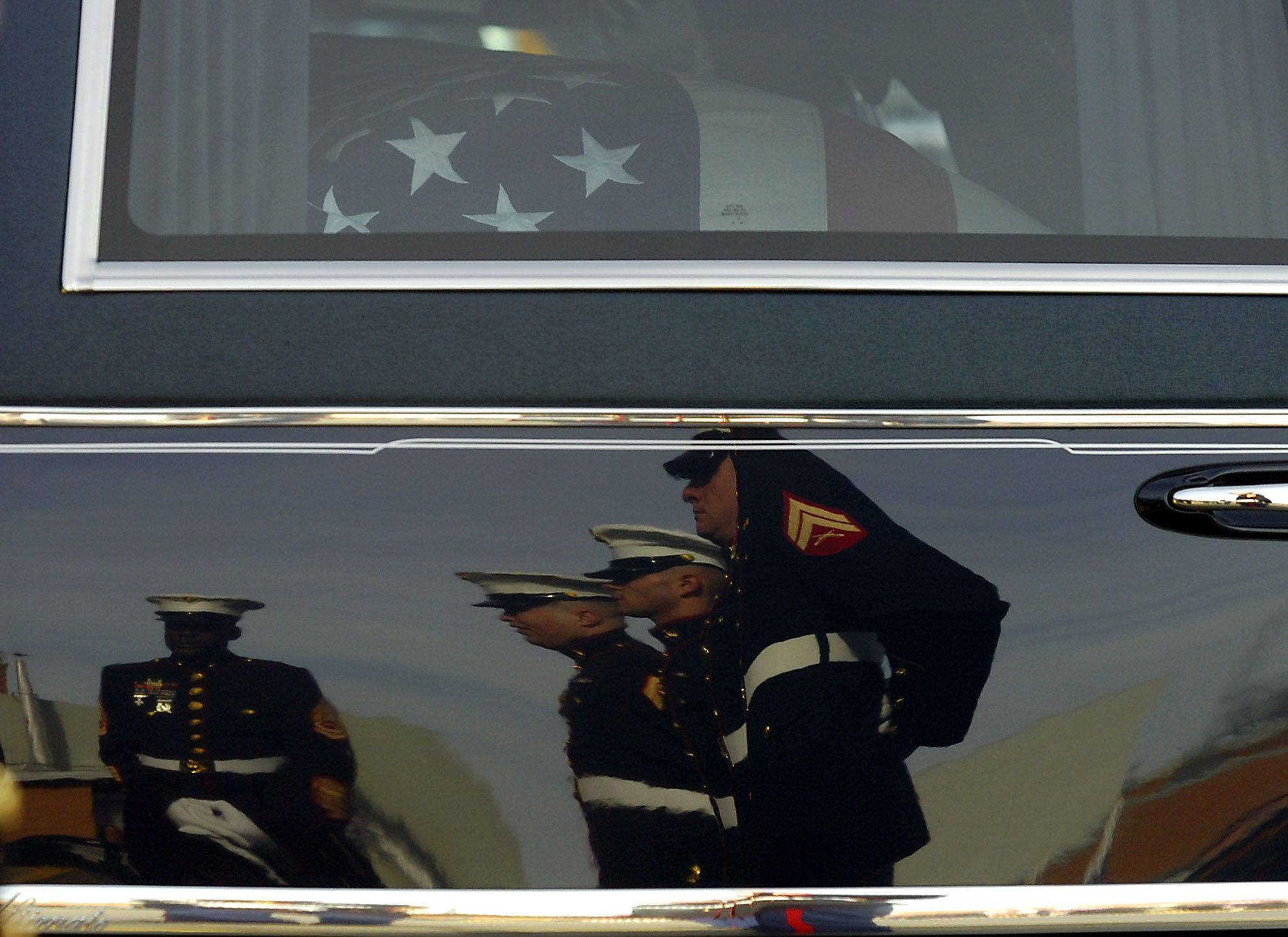 The reflection of several Marines adorns the hearse carrying the coffin of Lance Corporal James Stack just before it was taken in to Prospect High School for the memorial service on Saturday.