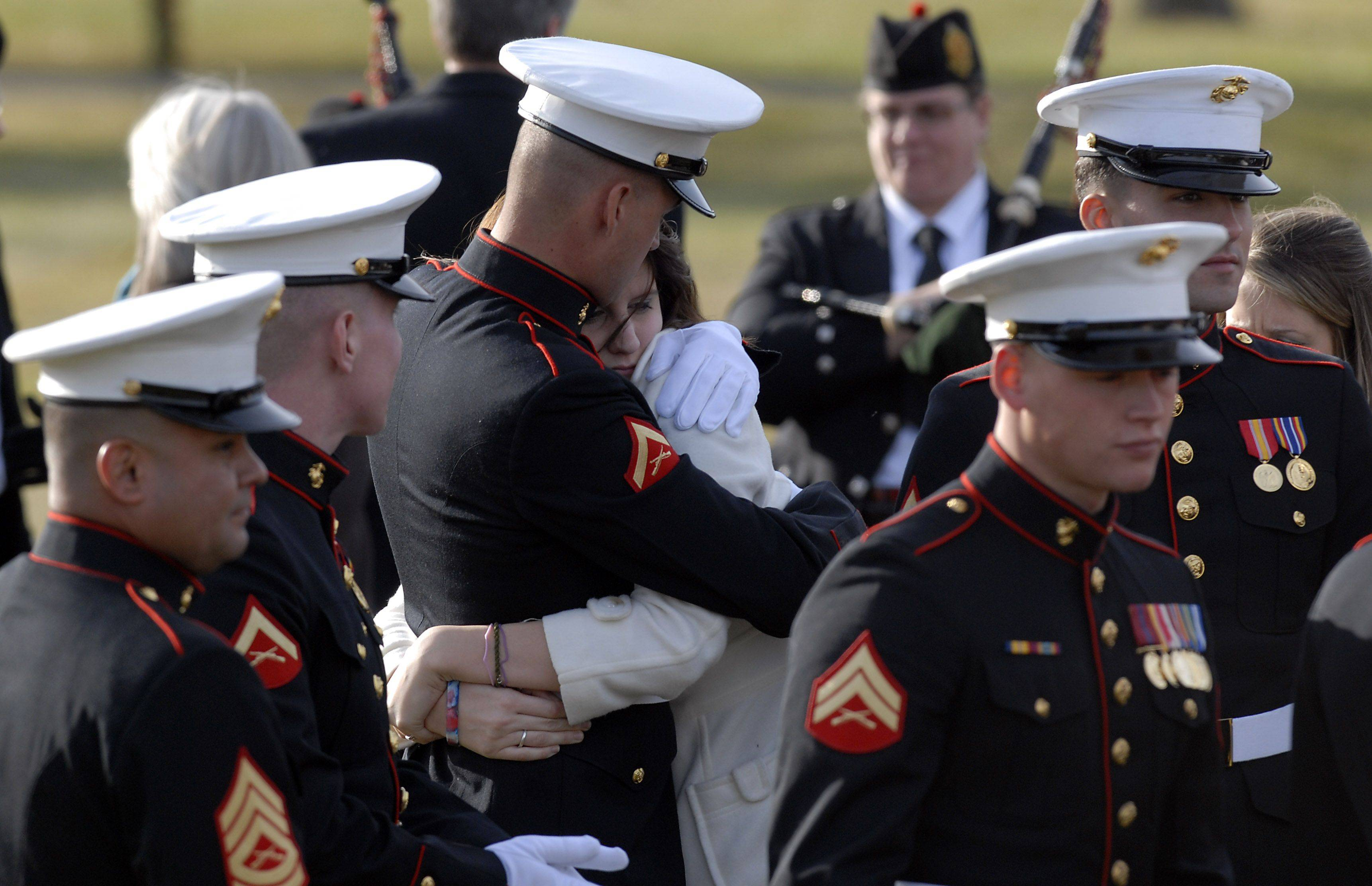 Katie Stack, wife of fallen Marine, Lance Corporal James Stack is hugged by a fellow Marine as she arrives at Memory Gardens in Arlington Heights on Saturday.