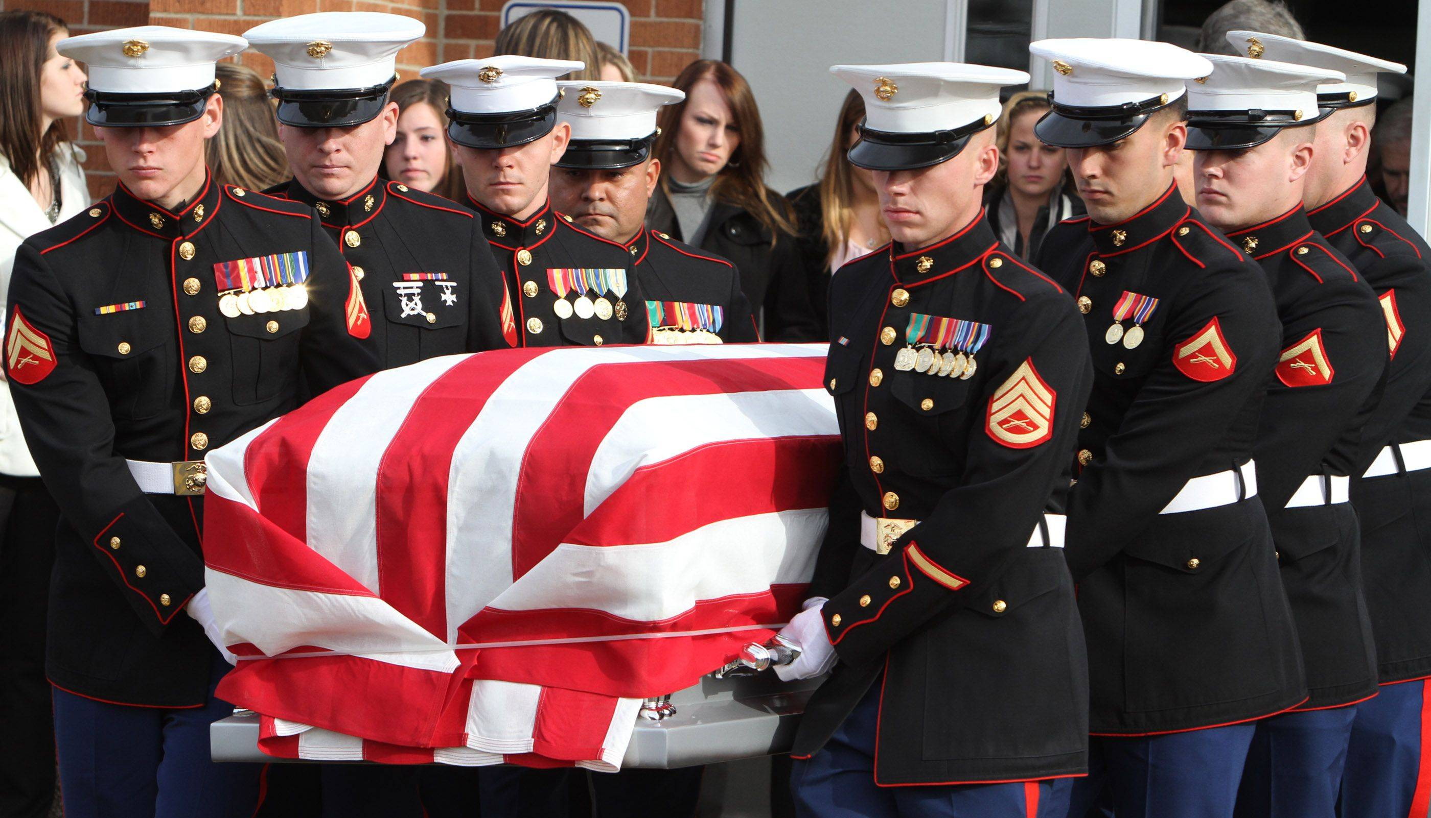 A marine honor guard carries the flag-drapped casket of 20-year-old Marine James Bray Stack, from services at Prospect High School field house in Mt. Prospect on Saturday, November 20, 2010.