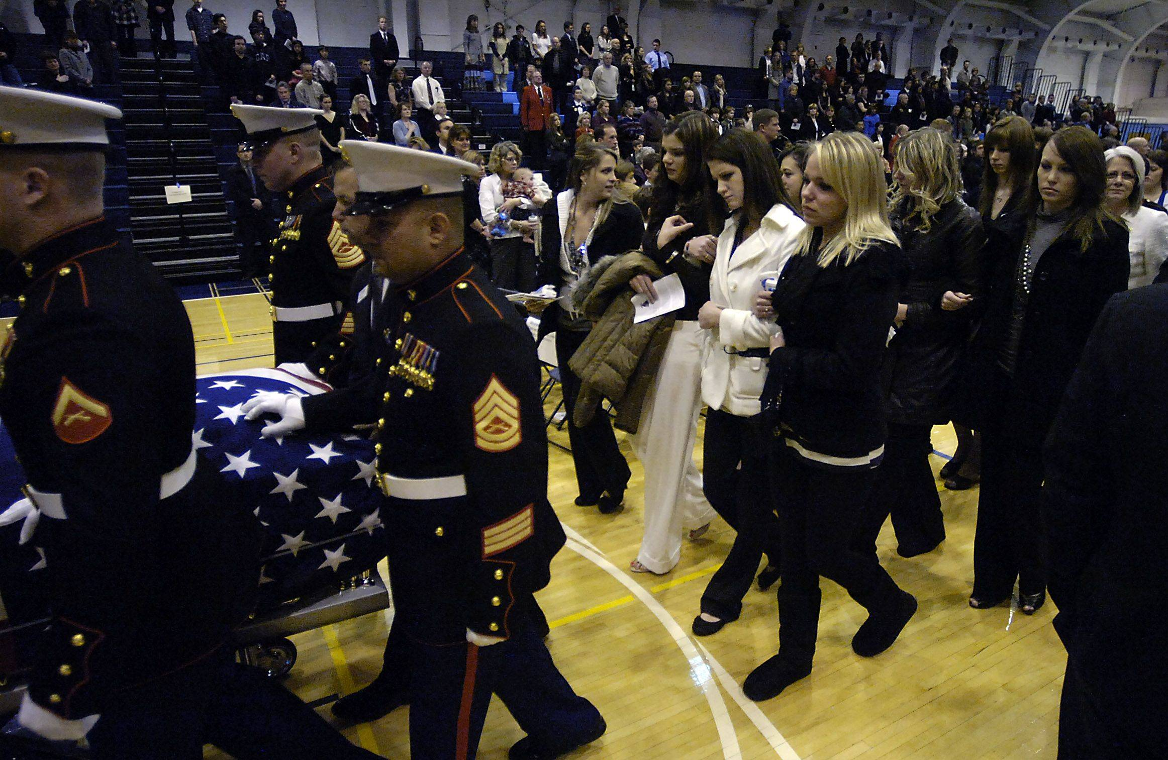 Katie Stack (in white) follows her husband, fallen Marine Lance Corporal James Stack, out of Prospect High School gymnasium after the memorial service in his honor.