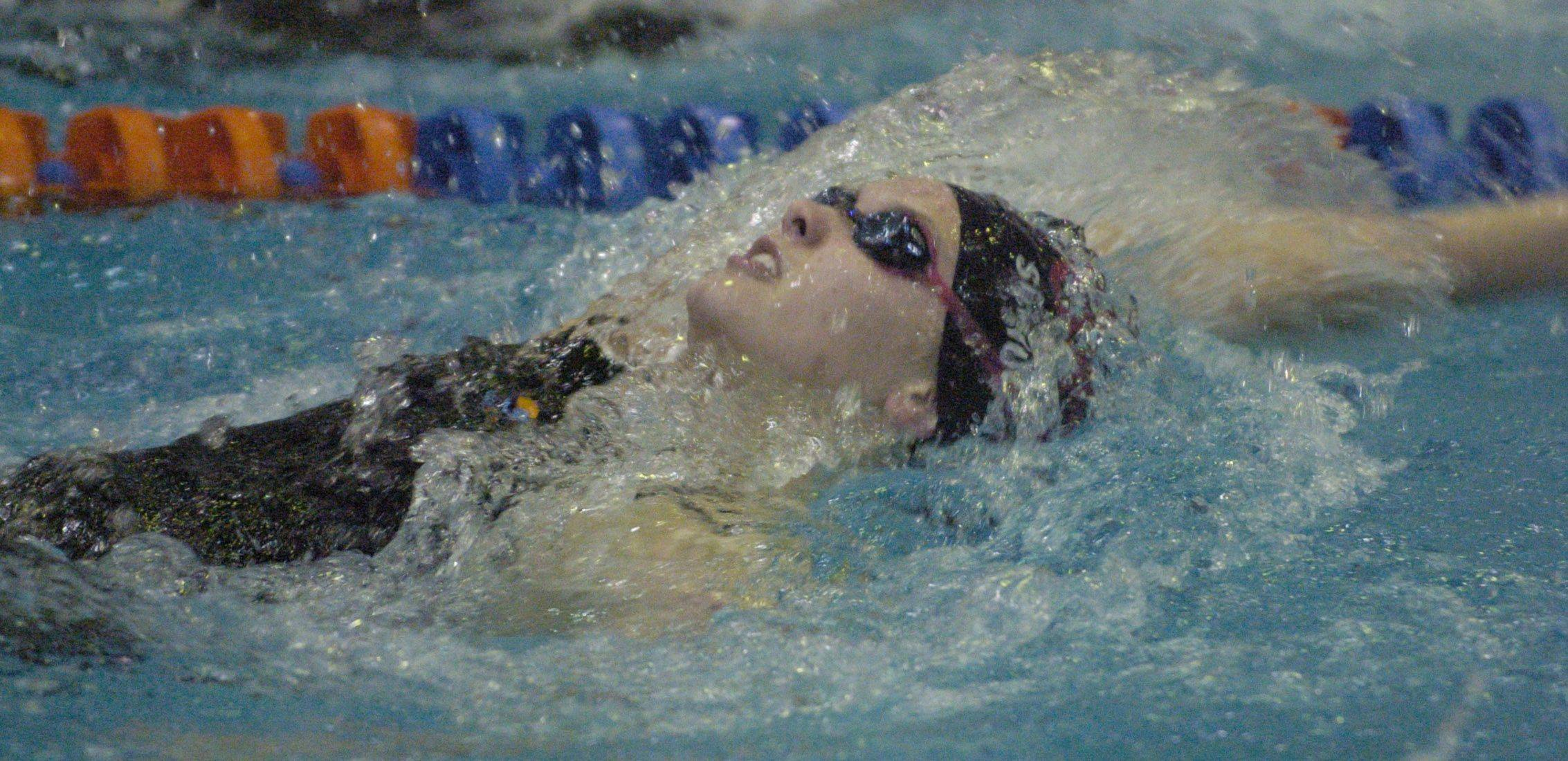 Schaumburg's Sammy Schuckles swims the 100-yard back stroke during Saturday's state swimming finals at Evanston.