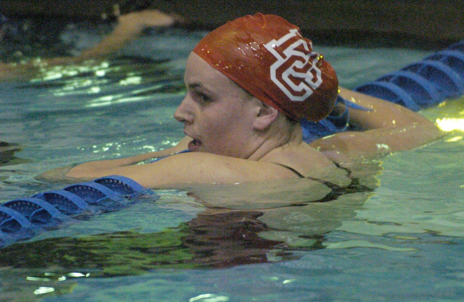 Colleen Champa of Dundee Crown rests on the lane line upon completion of her 100-yard breast stroke race during Saturday's state swimming finals at Evanston.