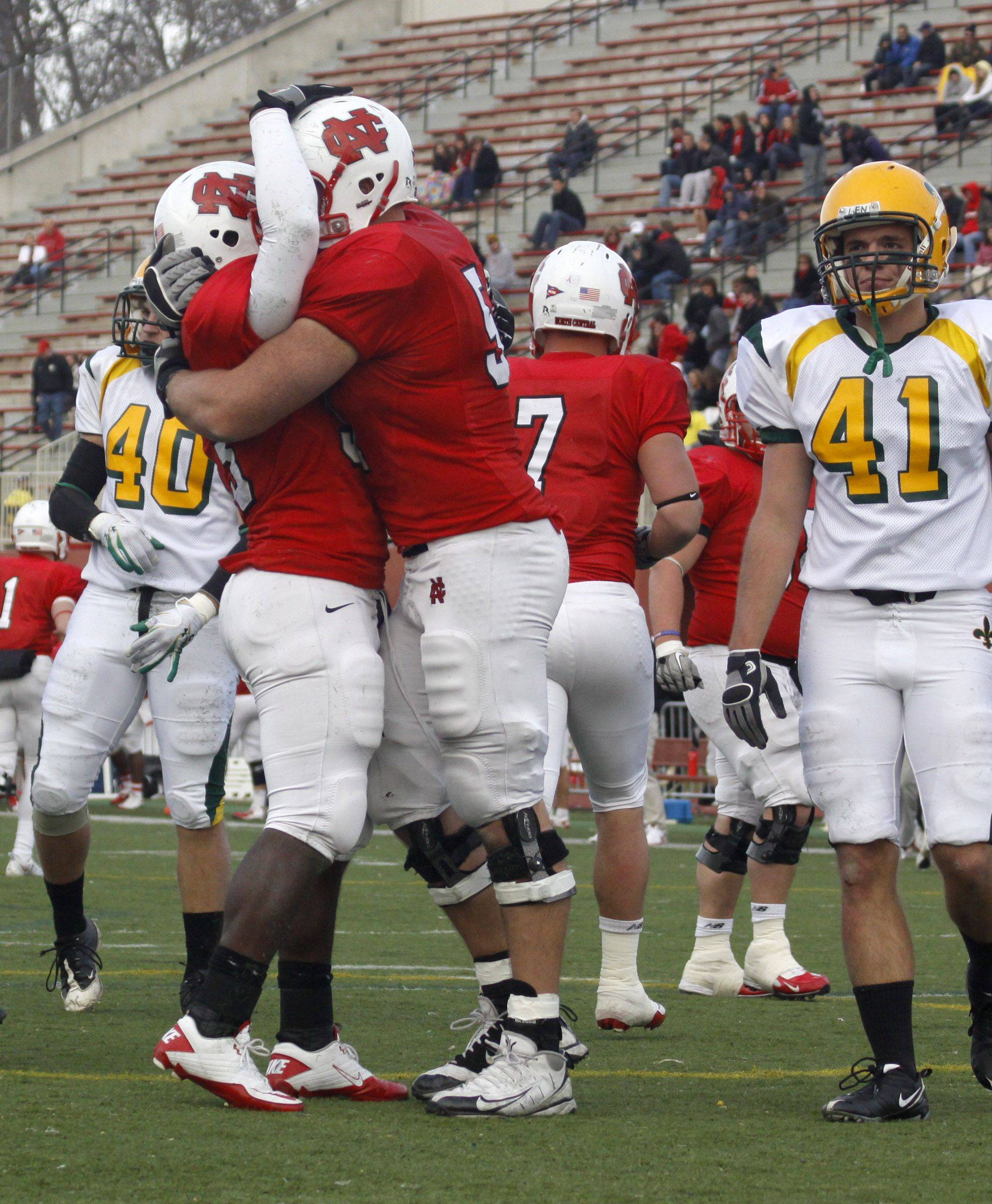 North Central College players Denzel Thompson, 33, and Will Thurn, 57, celebrate after Thompson scored a touchdown at Saturday's playoff football game against St. Norbert. North Central College went on to win 57 to 7.