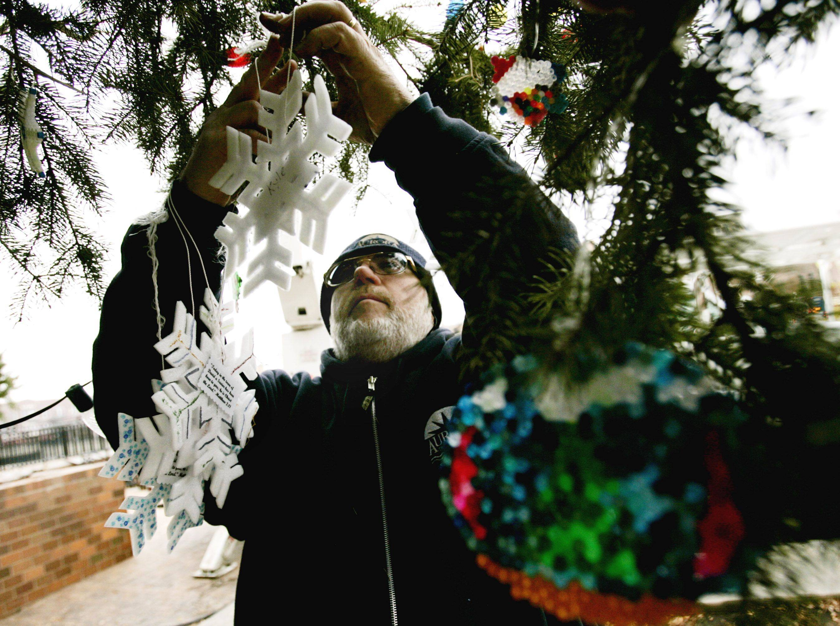 Aurora Street Department employee Don Sadler hangs ornaments on the holiday tree, in preparation for the ceremony at North Island Center in Aurora.