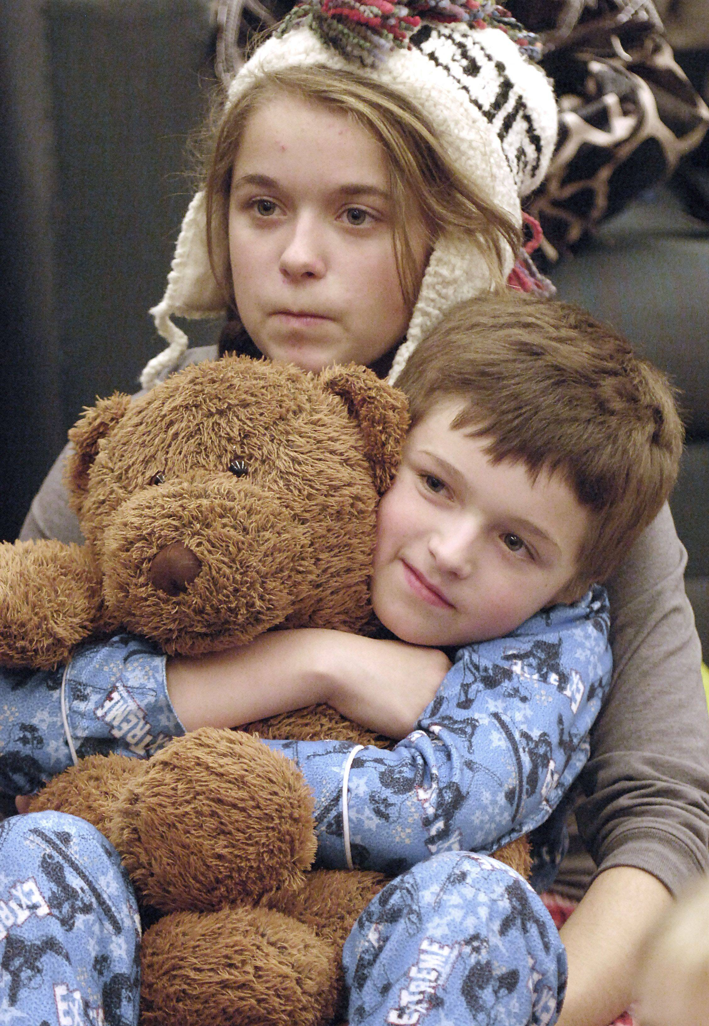McKenzie Palm, 15, and little brother, Keegan, 8, of Sycamore cuddle up and listen to Kane county judges read books aloud in the Law Library at the Kane County Judicial Center in St. Charles on Wednesday, November 17. McKenzie has been coming to the annual reading event since she was a little girl.