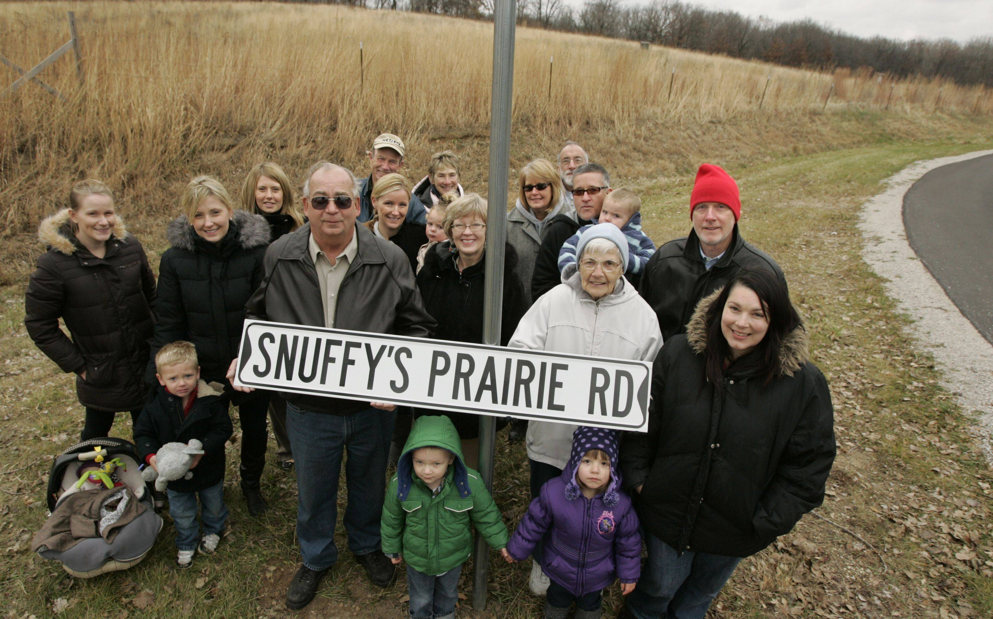 "Don ""Snuffy"" Smith's family, including several great-grandchildren, gathers at the prairie that bears his name in Dundee Township in honor of the street being re-named Snuffy's Prairie Road. Holding the new street sign are Don's widow Betty Smith and Dundee Township Highway Commissioner Larry Braasch. Nearby resident Steve Keibler and Dundee Township Supervisor Sue Harney, also in the photo, were instrumental in getting the road re-named for Don who was a lifelong resident of the township. The road was previously named Hickory Avenue. According to township rules, every resident of the subdivision needed to sign off on the new street name, and Keibler, in rear with baseball cap, got everyone on board with the change."