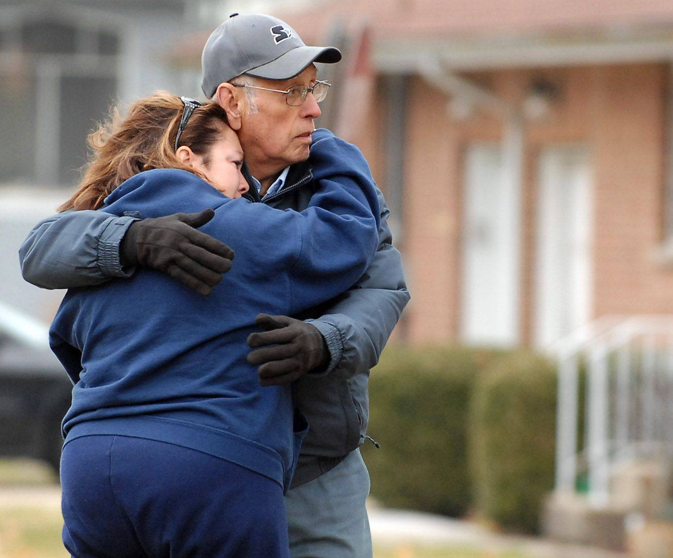 Family members Nikkole Bennett and Al Martinez comfort each other outside the home of Josephine Guerra, who died in a house fire overnight at 653 Prospect Street in Elgin. Bennett, from Belvidere, is Guerra's niece and Martinez, from St. Charles is her brother-in-law.