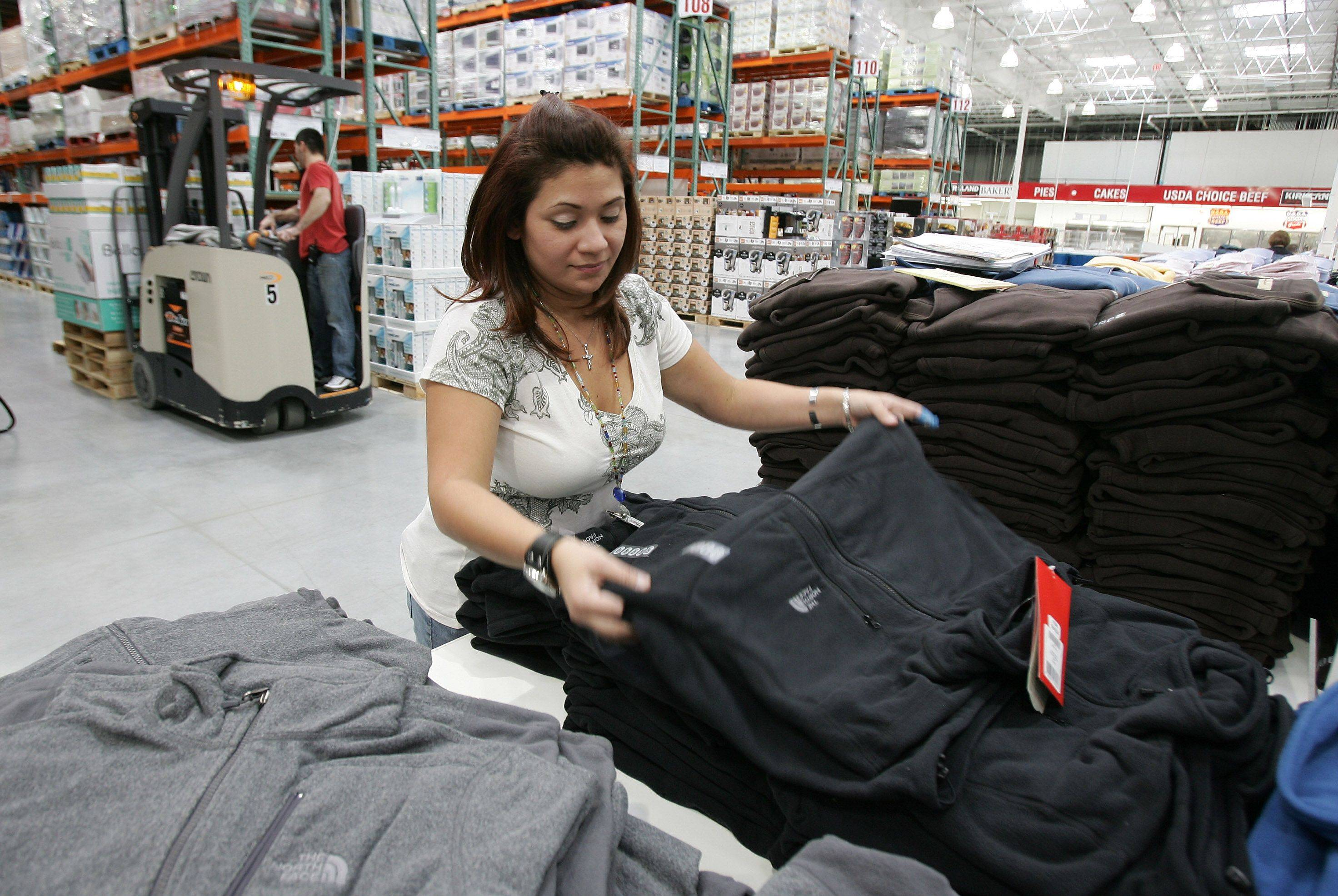 Linda Garcia-Martinez folds clothes in preparation for the opening of Costco in Mettawa Saturday morning.