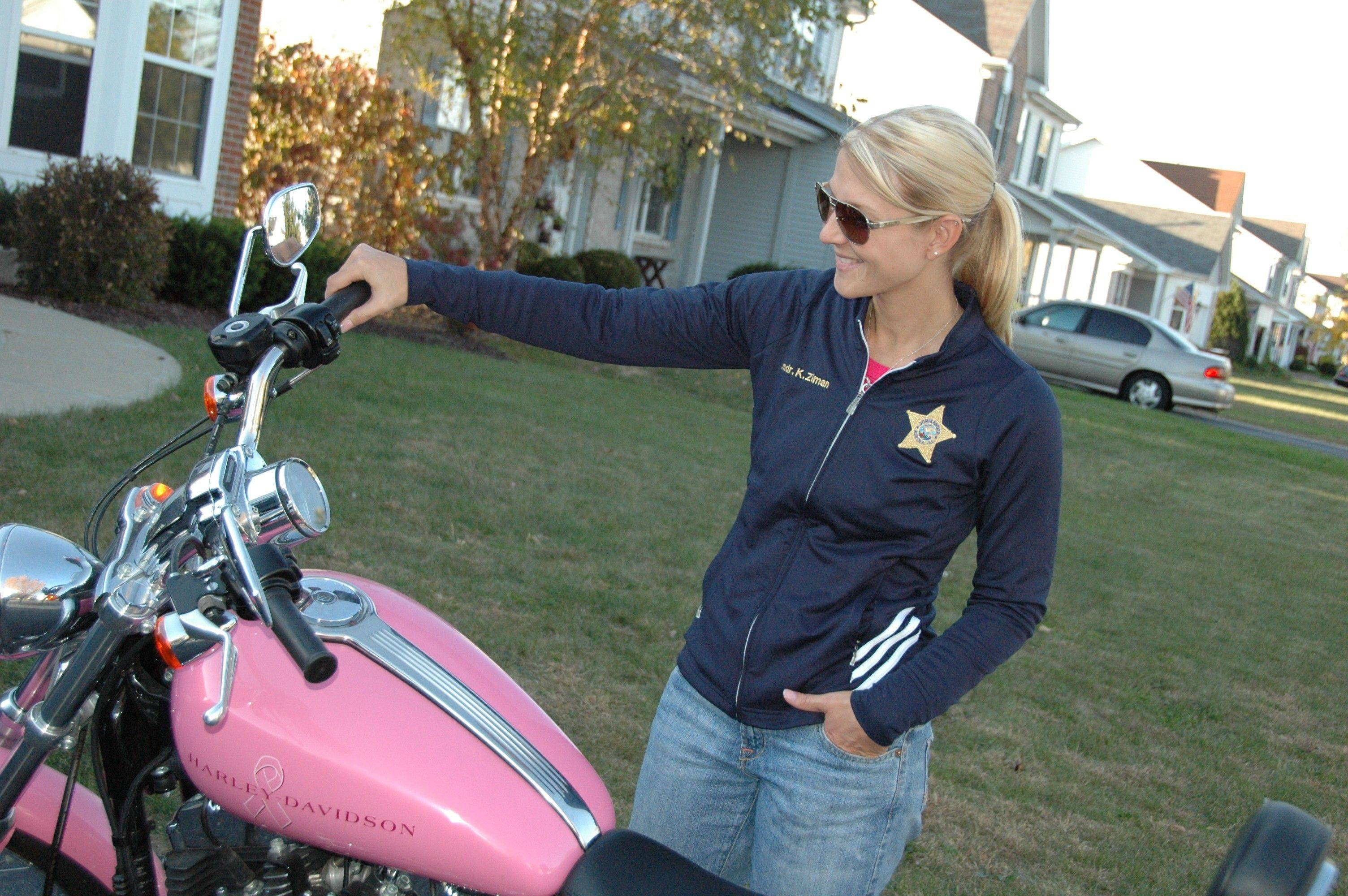 Kristen Ziman, commander of the Bureau of Neighborhood Policing for the Aurora Police Department, inspects her pink Harley-Davidson motorcycle.