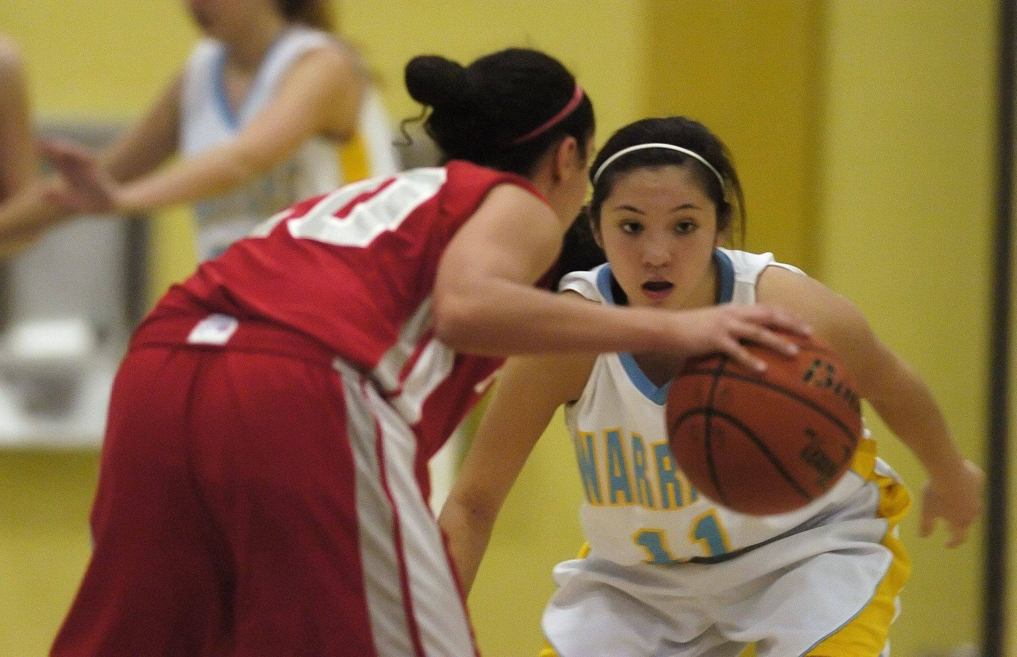Nia Pappas of Palatine moves past Amanda Hoye of Maine West during girls varsity basketball action in Des Plaines