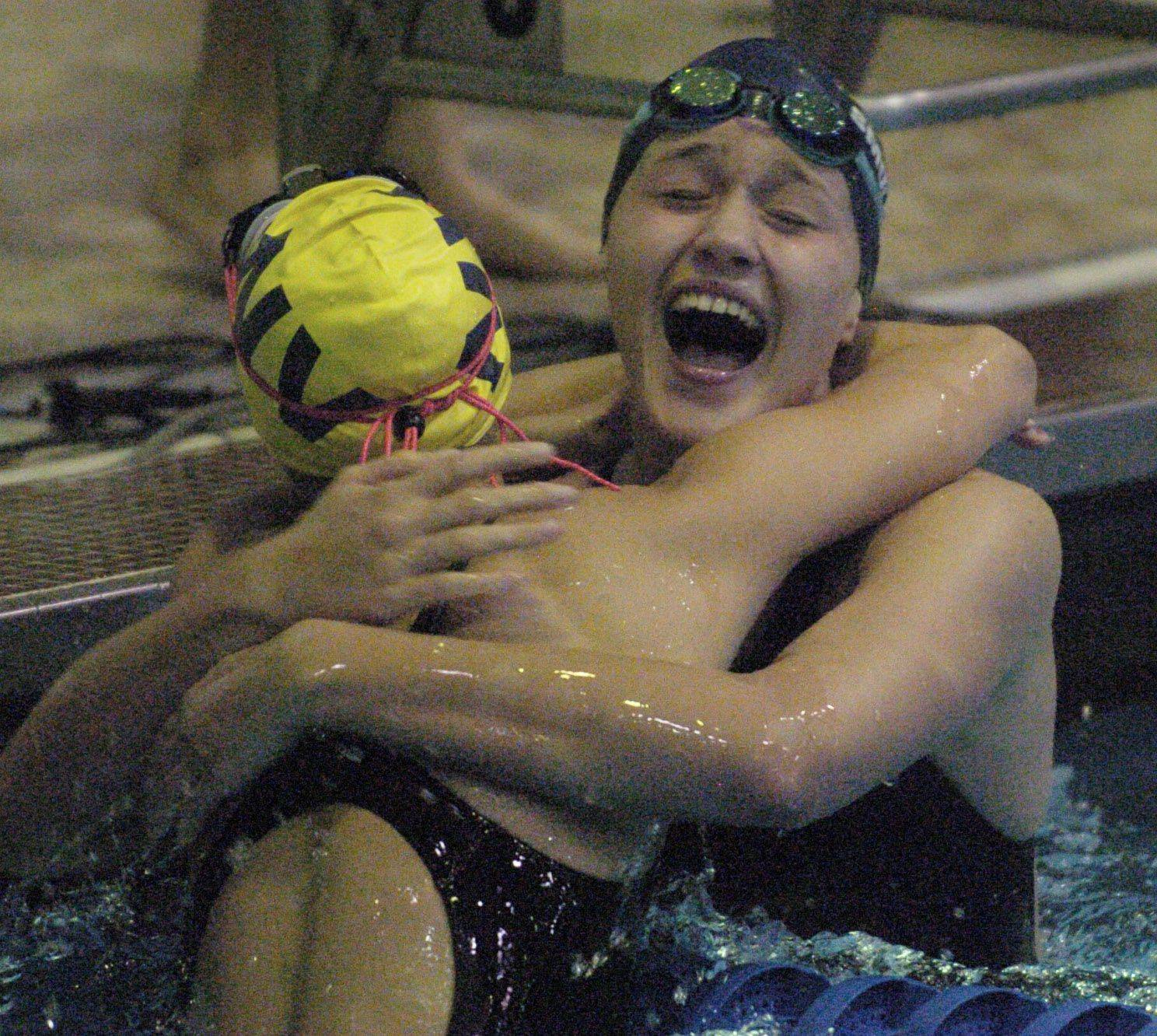 Olivia Smoliga of Glenbrook South, right, hugs Gia Dalesandro of Neuquaq Valley after breaking the state record in the 100-yard back stroke during Friday's girls state swimming prelims at Evanston High School.
