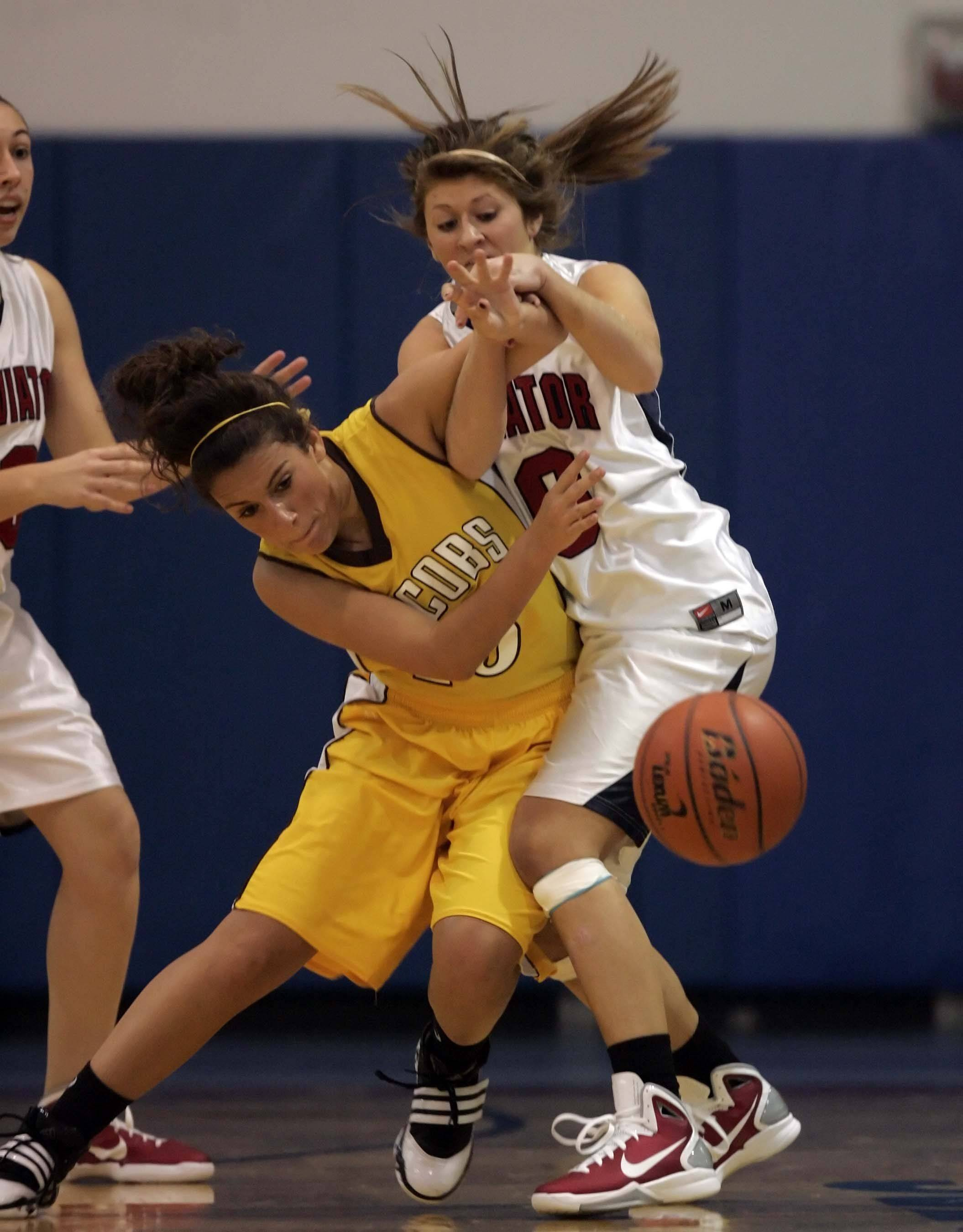 Jacobs' Payton Berg, 15, battles St. Viator guard Katie Gavin, 10, for a loose ball during the Dundee-Crown High School girls basketball Thanksgiving tournament Friday in Carpentersville.