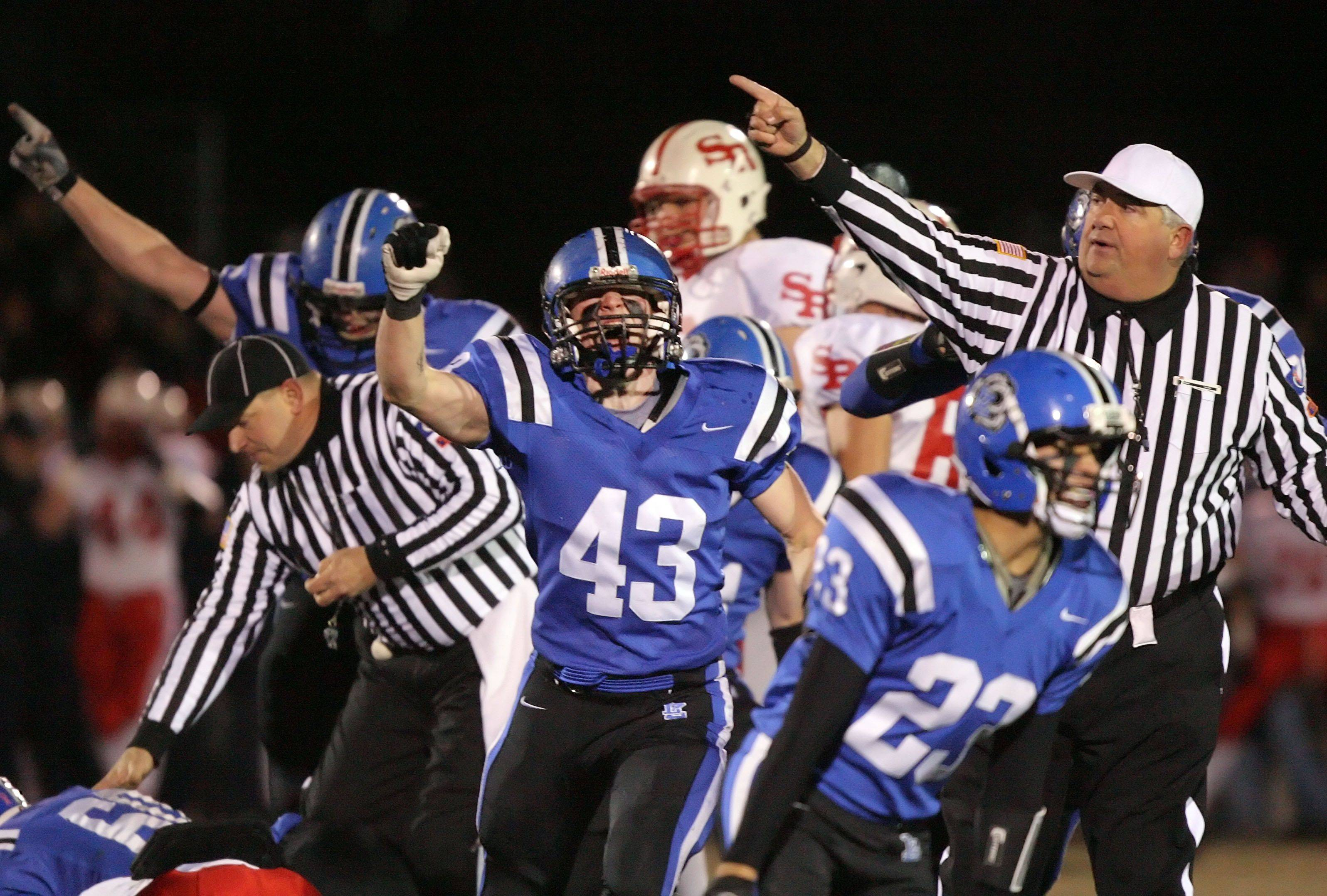 Lake Zurich's defense celebrates after recovering a St. Rita fumble during the IHSA Class 7A football semifinal game Saturday night in Lake Zurich.