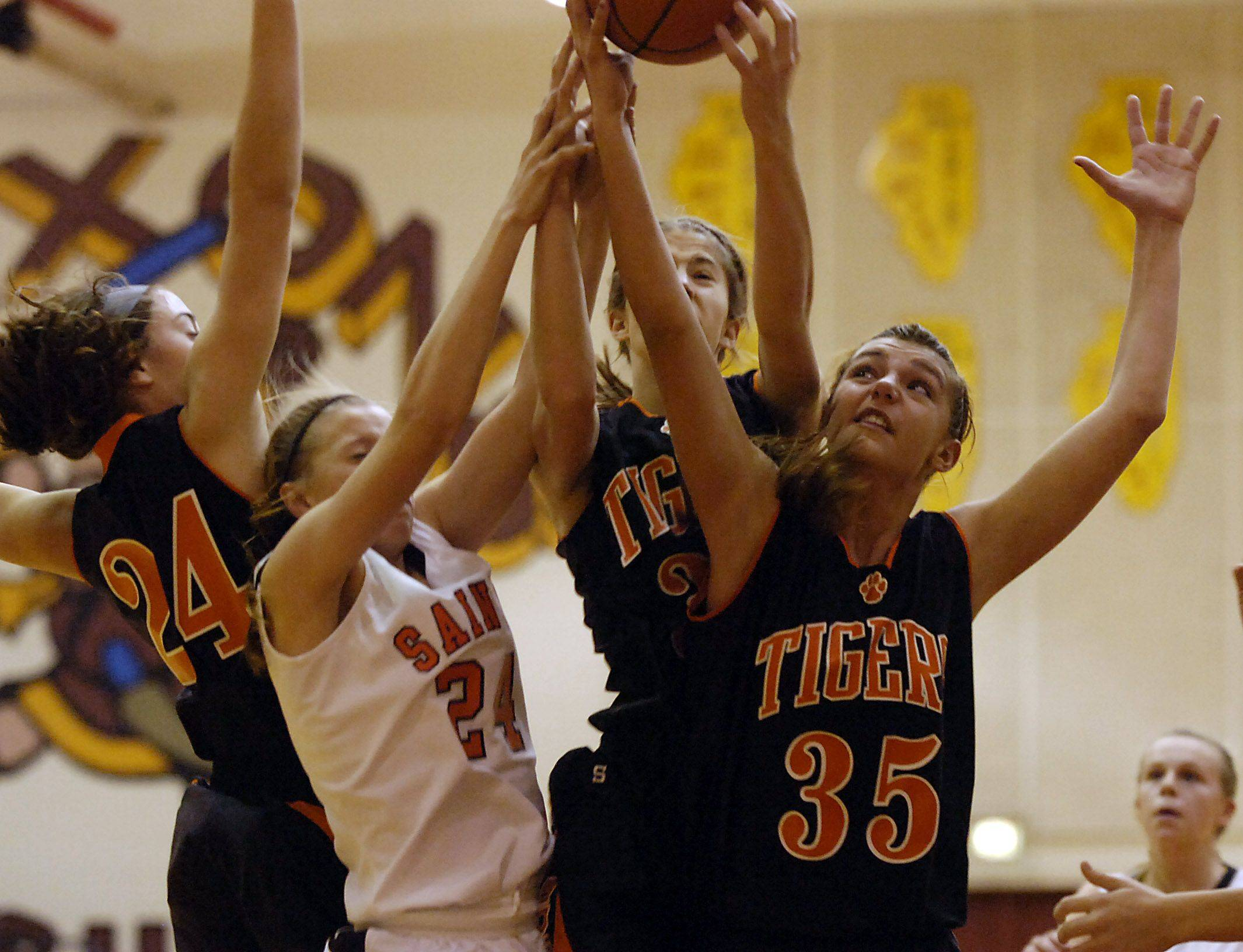 Wheaton Warrenville South's Allie Zappia, right, battles for the rebound with teammate Kasey Gassensmith and St. Charles East's Laney Deckrow in the girls basketball tournament in Schaumburg.