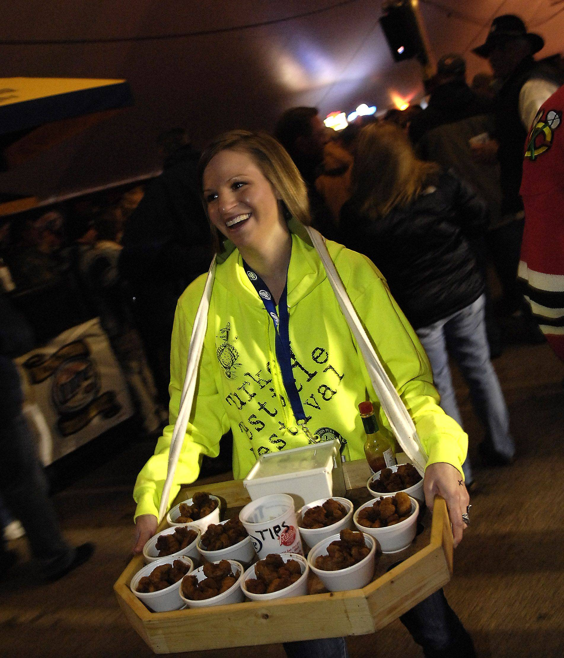 Megan Chamberlain finds an opening in the crowd as she moves product during the Huntley Turkey Testicle Festival at Parkside Pub Wednesday.