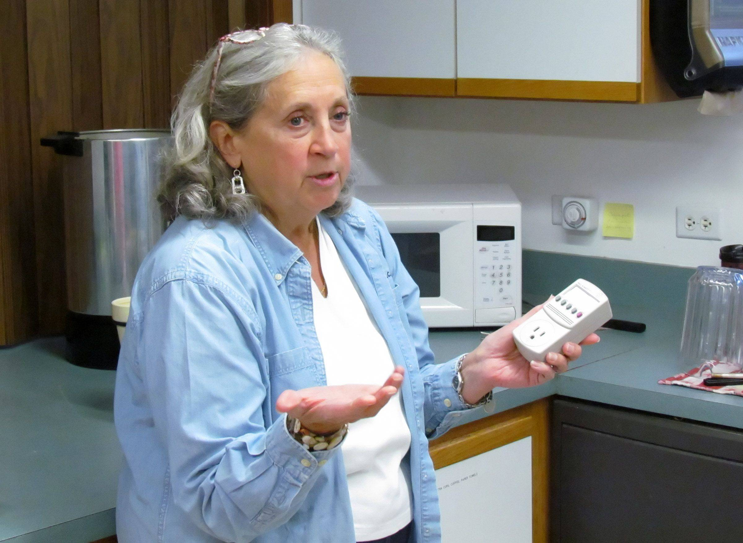 In the kitchen at St. Timothy Lutheran Church in Naperville, Kay McKeen uses a Kill A Watt meter to tell how much power the microwave oven uses even when it is off.