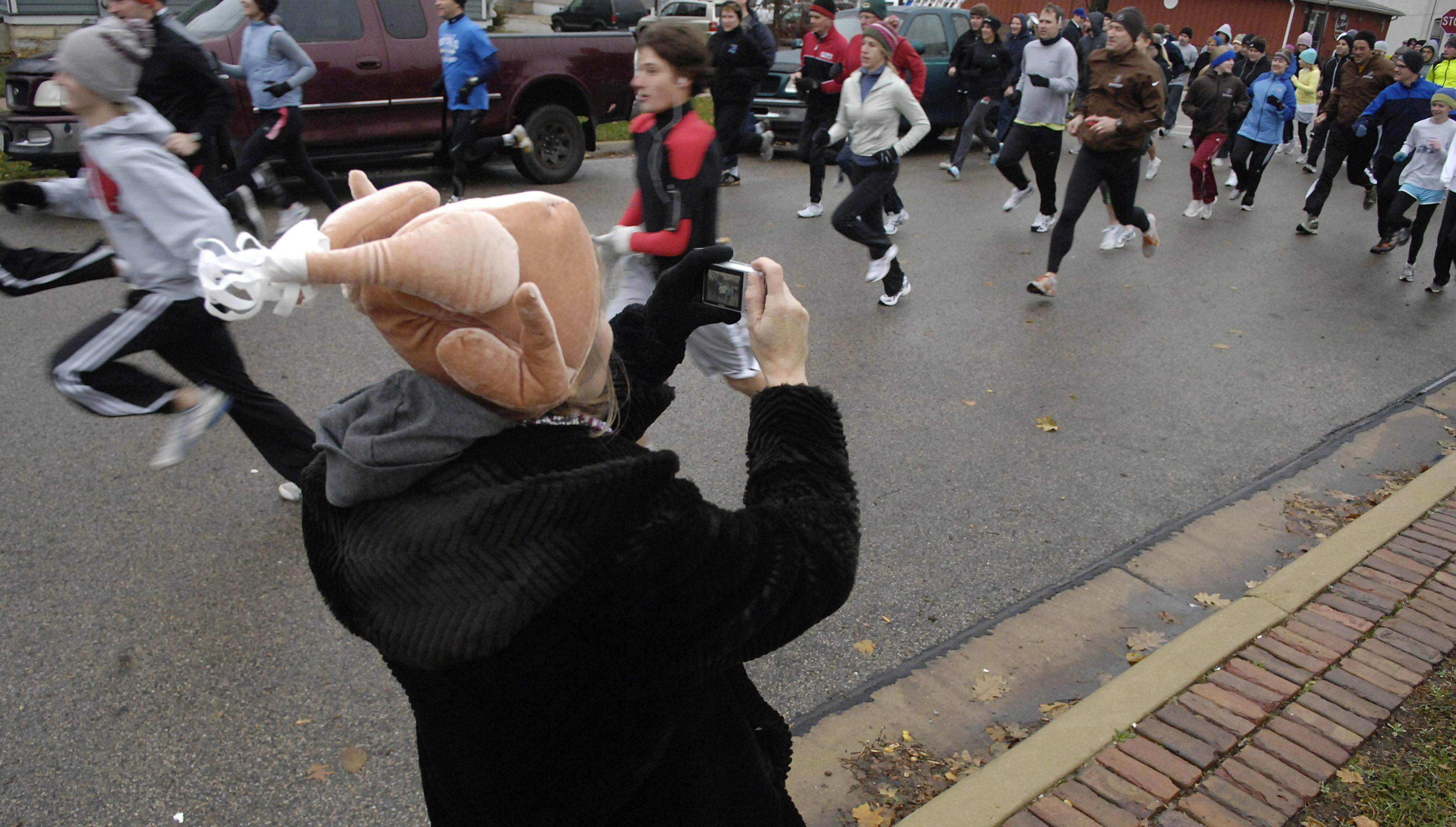 "Nancy Smith of West Dundee takes photos of her daughter Laurie Conley and son-in-law Ben Conley of Chicago as they take off at the starting line in the ""Thanks A Lot! Turkey Trot 5K Fun Run and Walk"" in the Gifford Park neighborhood in Elgin on Thanksgiving Day. Runners were asked to bring non-perishable food items which will be donated to the Northern Illinois Food Bank in Elgin�s First Congregational Church Food Pantry."