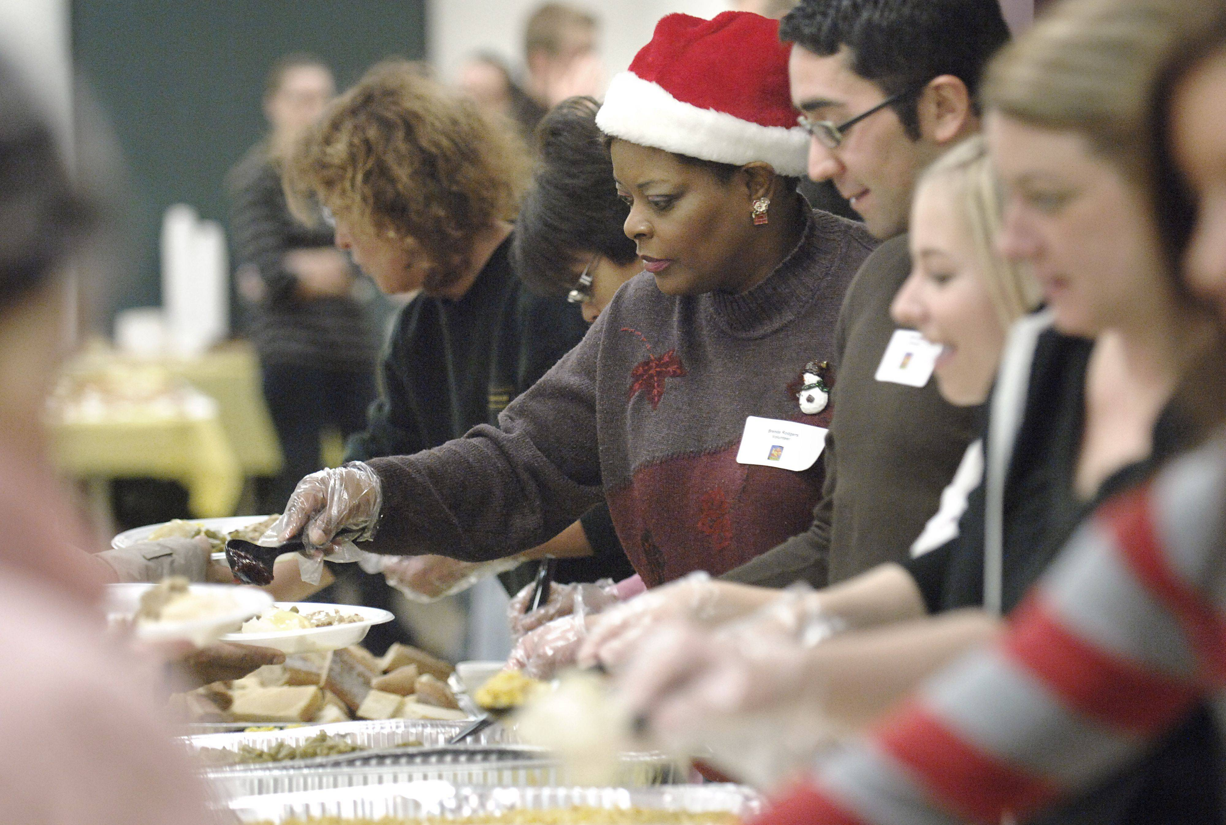 Brenda Rodgers of Elgin, wearing a Santa hat, serves food at the community Thanksgiving dinner at the Hemmens Cultural Center in Elgin on Thanksgiving Day. Sixty-five turkeys were prepared for the feast.