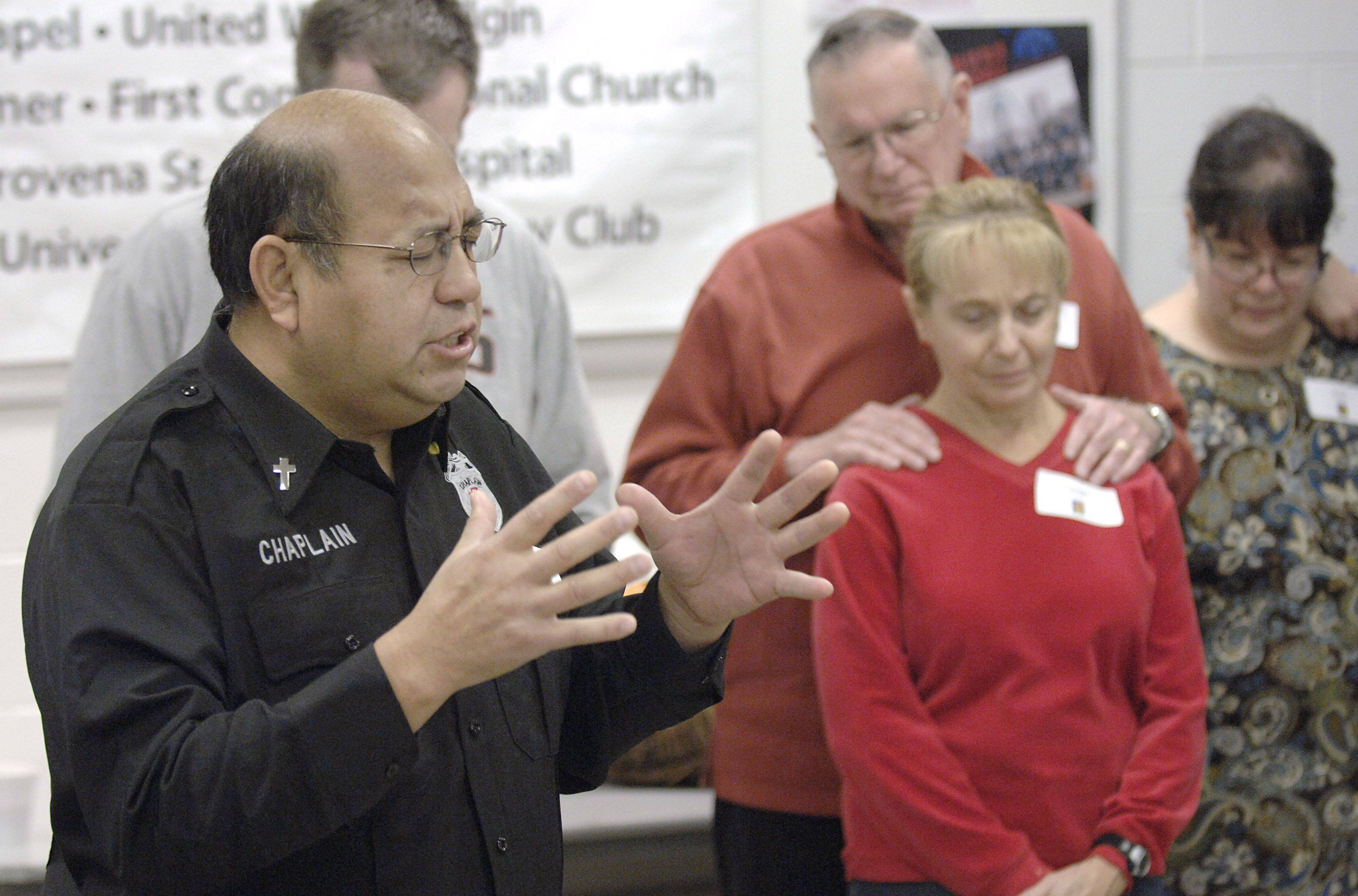 Elgin Police Community Chaplain Henoch Fuentes of Elgin leads volunteers in prayer before the start of the community Thanksgiving dinner at the Hemmens Cultural Center in Elgin on Thanksgiving Day. Fuentes is also a Salvation Army pastor in Elgin.
