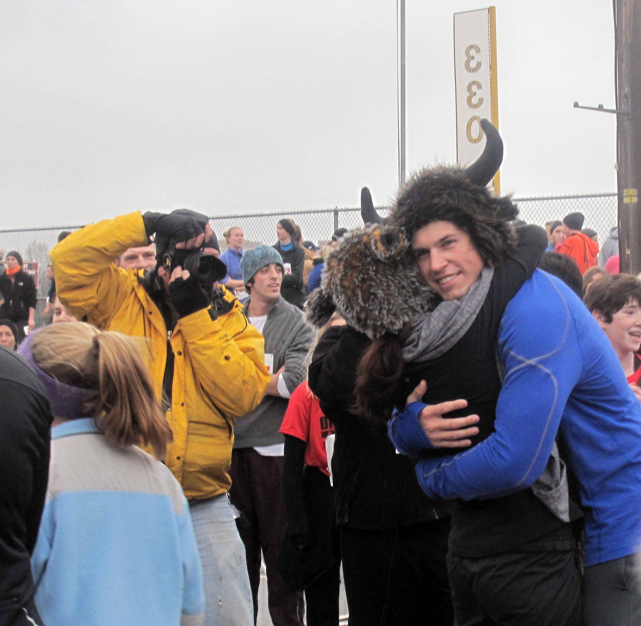 Warrenville resident Colton Antos hugs his fiancee, Brittany Acosta, after she accepted a marriage proposal after Thursday's Turkey Trot 5K run in Naperville. The couple was also celebrating their seventh anniversary