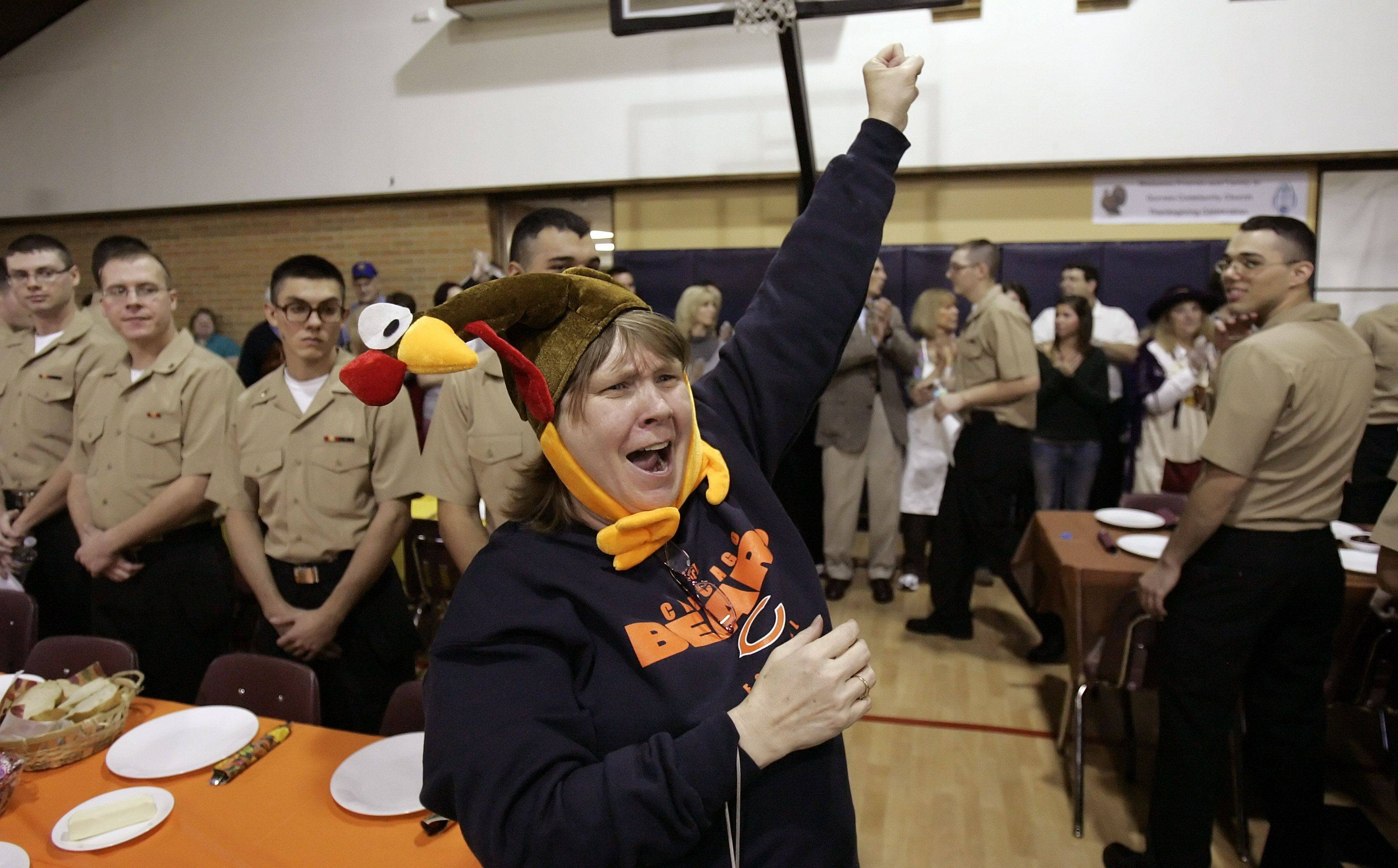 Gurnee Community Church member Debbie Krueger of Gurnee and members of the congregation cheer as 193 sailors from Recruit Training Command of Great Lakes make their way to the dining room for a Thanksgiving feast with all the trimmings.