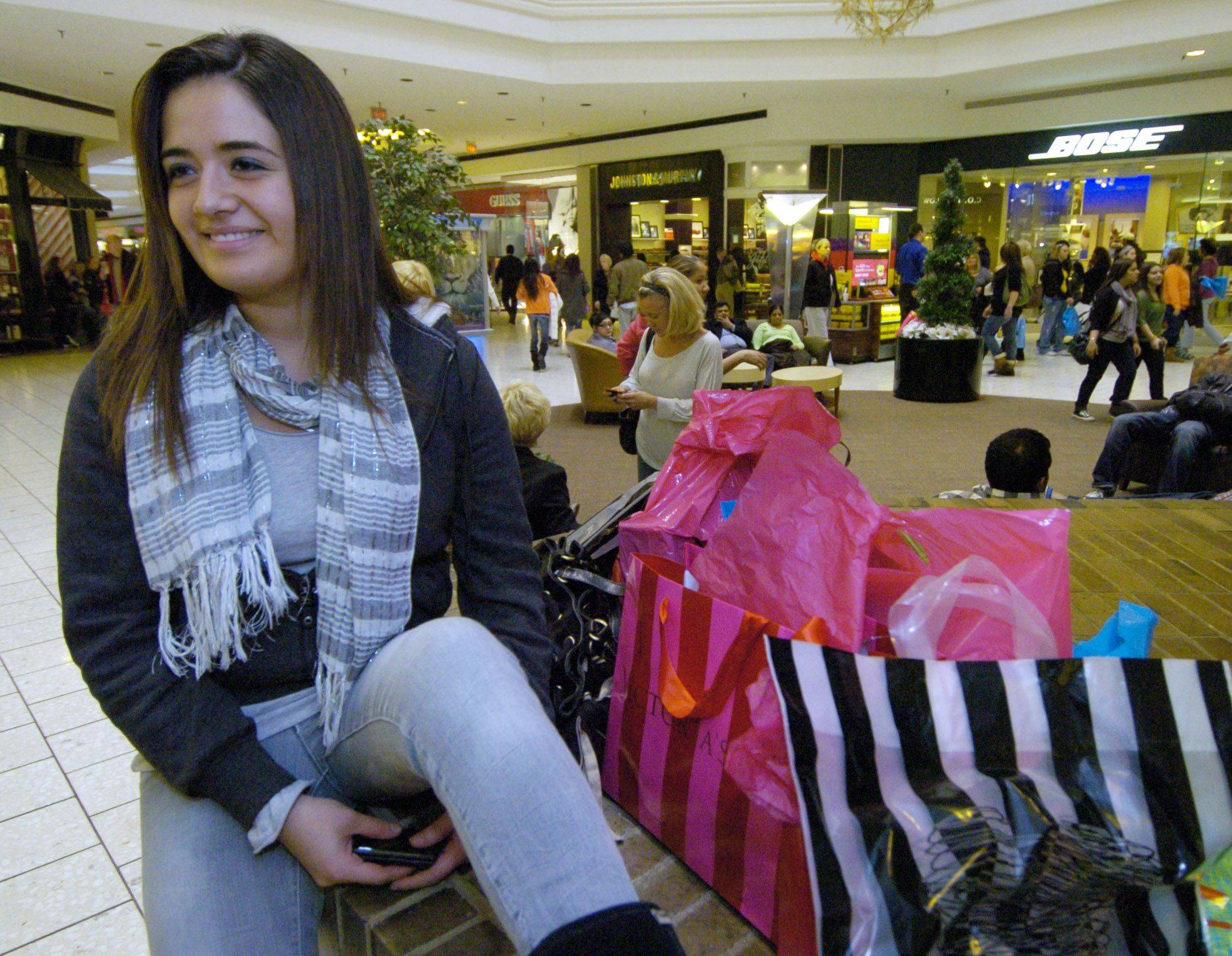 Tania Bravo of Addsion waits with the bags while a friend shops Friday.