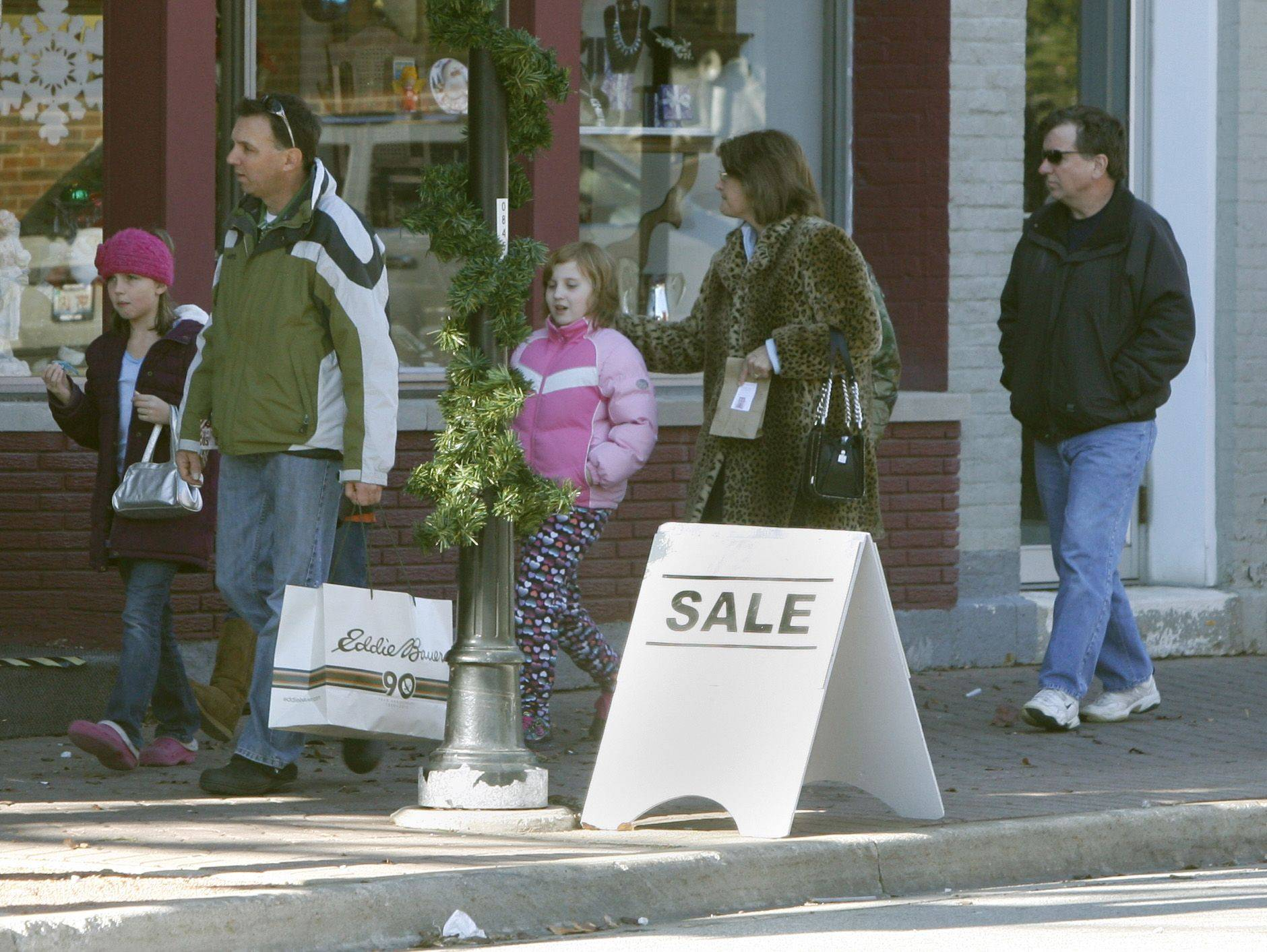 DANIEL WHITE/dwhite@dailyherald.com Shoppers make their way through the downtown intersection of Washington and Jefferson streets in Naperville Friday.