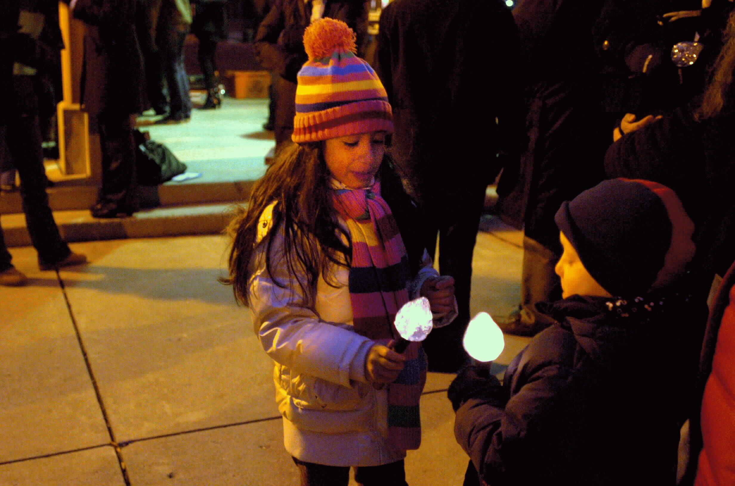 Six-year-old Giulia Ayala from St. Charles, and her friend, five-year-old Joey Jensen from St. Charles play with their flash llight torches that they received at the lighting of the holiday lights in Lincoln Park in St. Charles on Friday night.