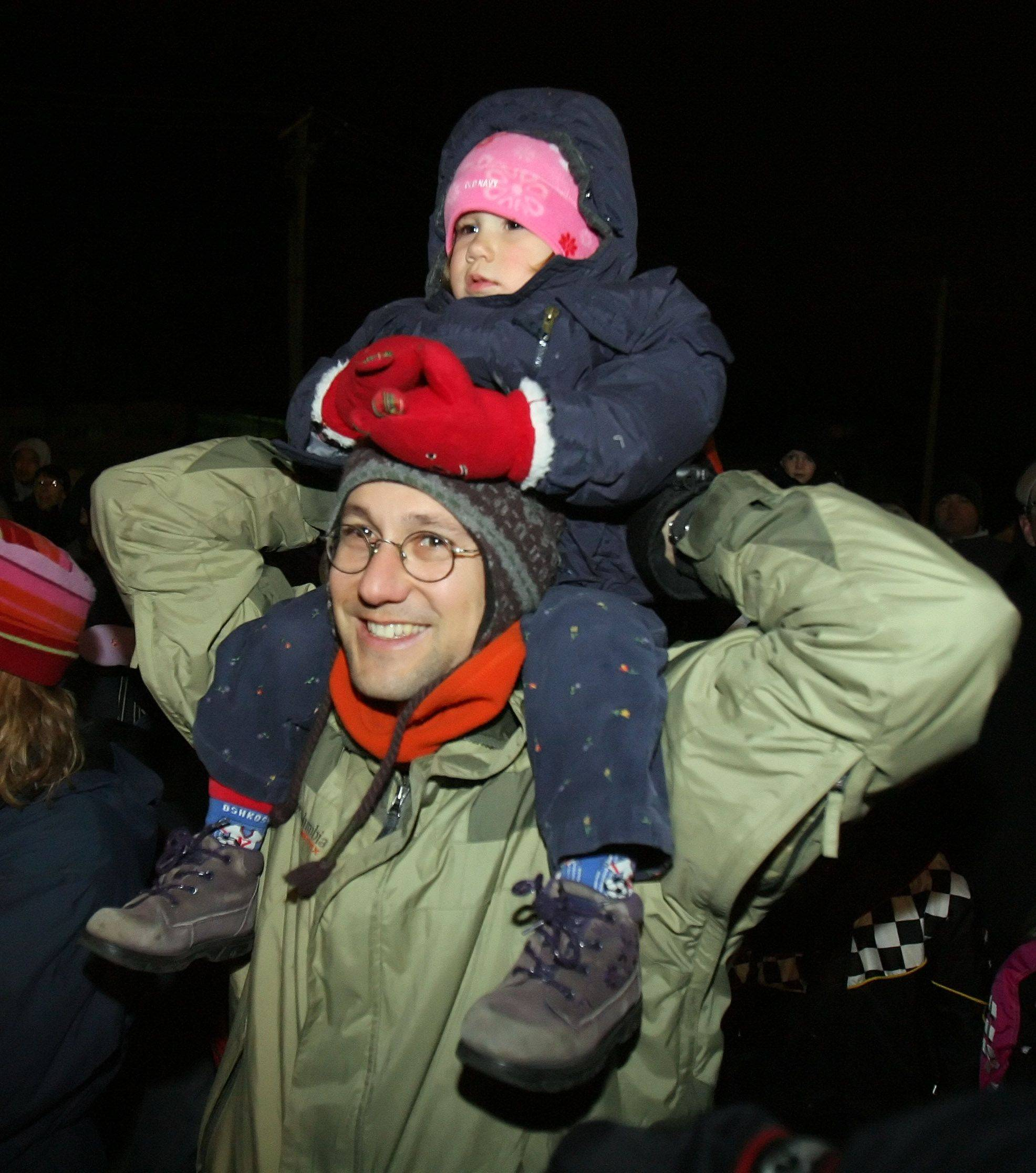 Louis Begin and his daughter Mira watch as santa arrives on a fire truck at Seymour Ave. and Center St. in downtown Grayslake Friday night.