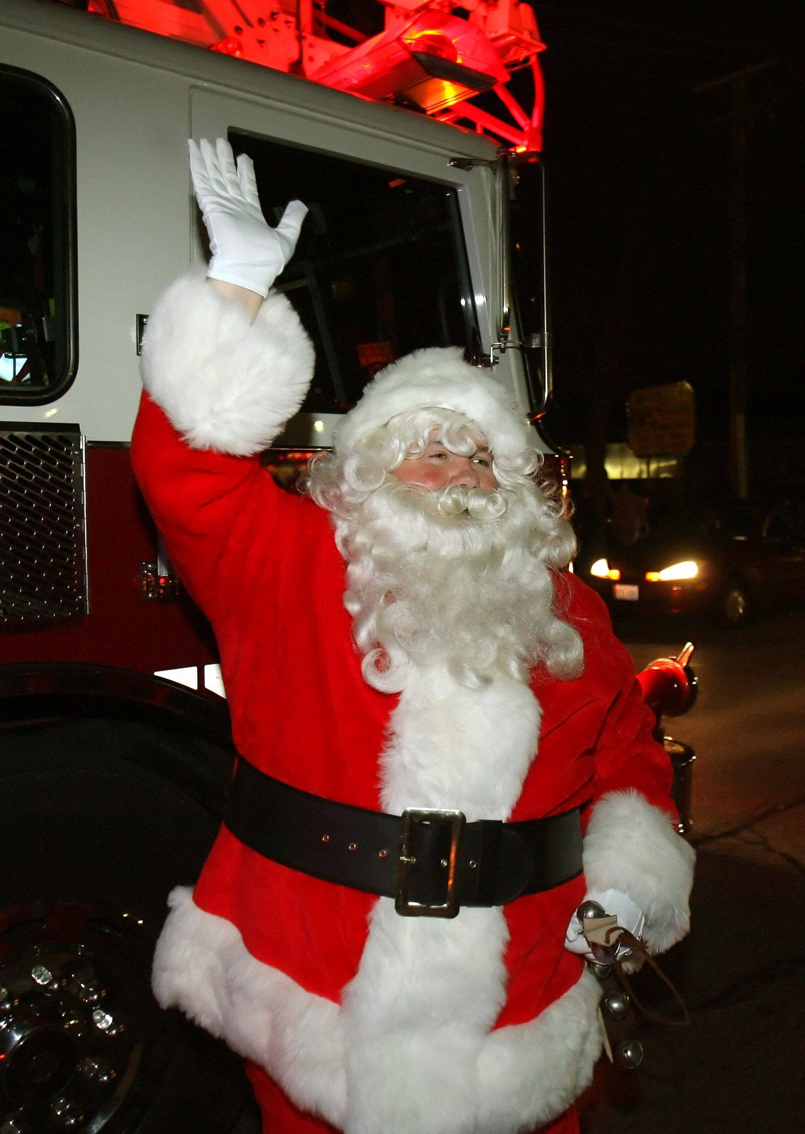 Santa waves to the crowd after arriving on a fire truck in downtown Grayslake Friday night.