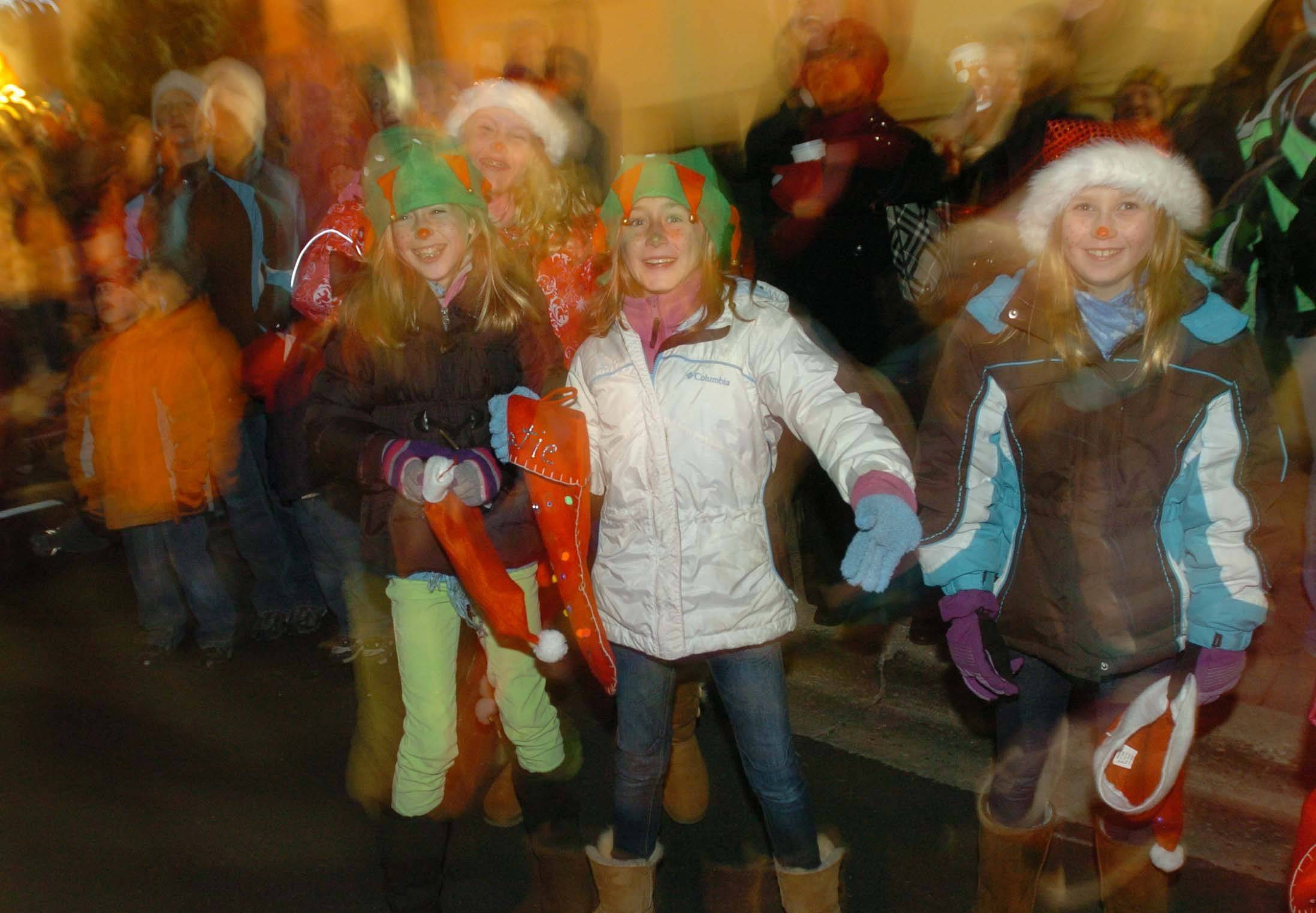 Children are all smiles during the parade at Naperville's Hometown Holidays celebration Friday. They were watching Santa drive the route.
