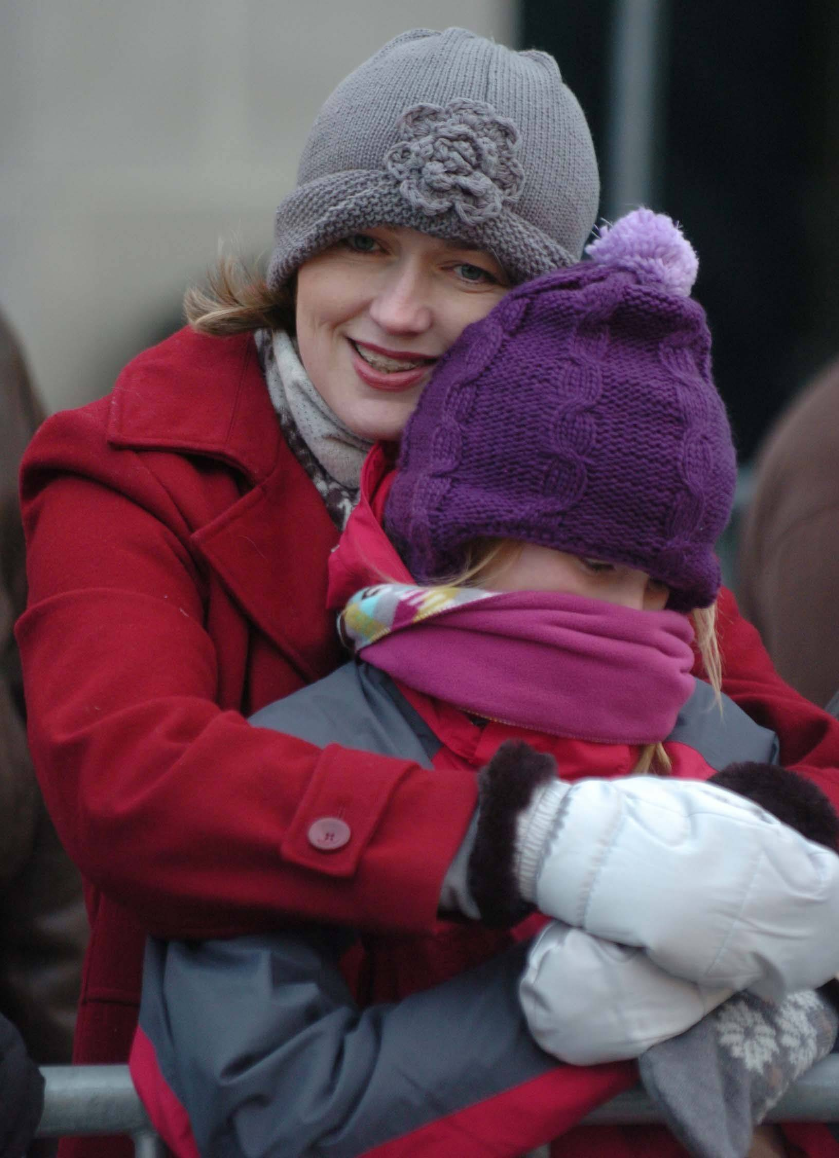 Monika Sofia and her daughter Blacha, both of Downers Grove, cuddle to keep warm during the Naperville's Hometown Holidays celebration Friday.