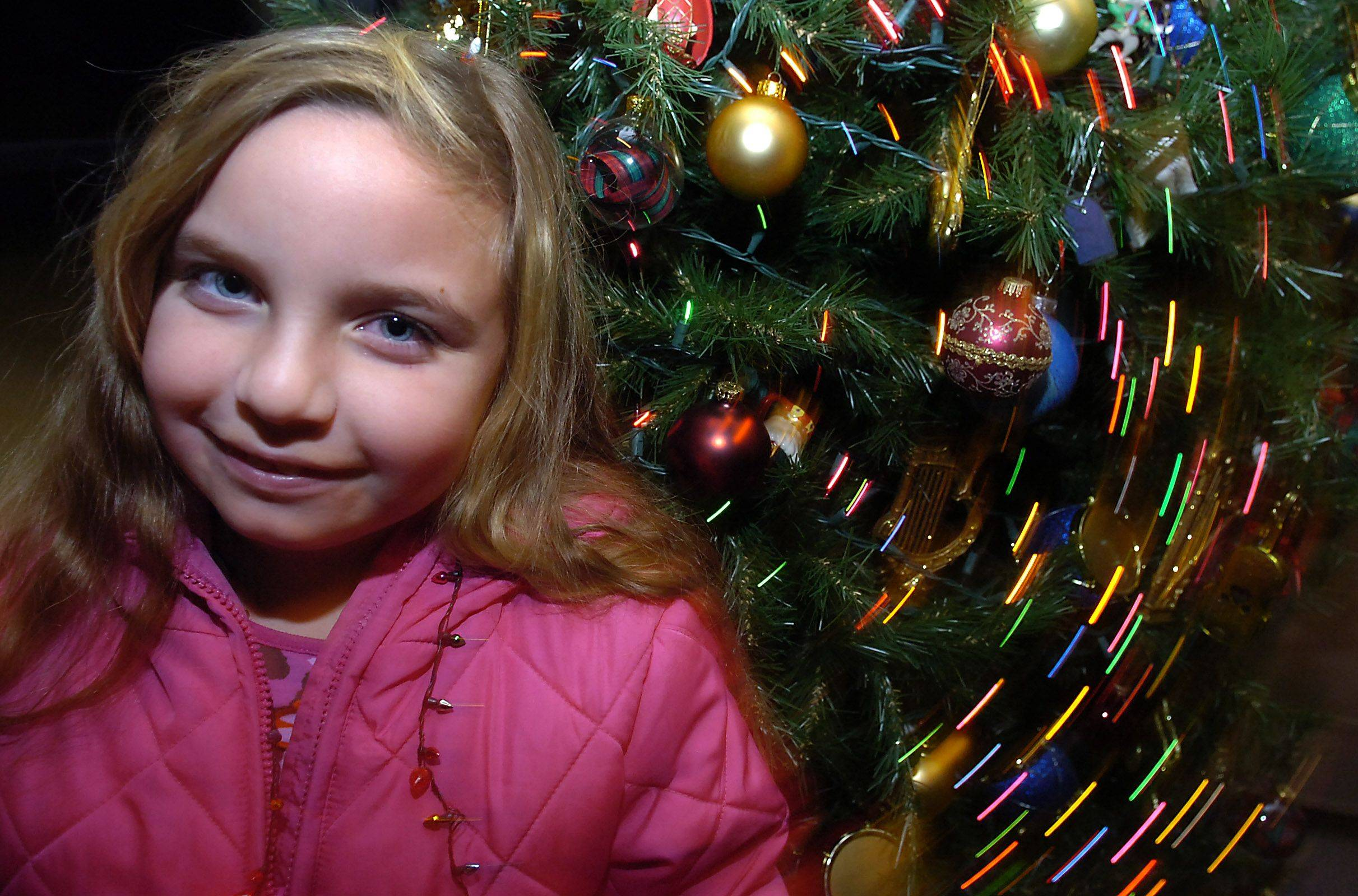 Allison Mamrot ,7, of Huntley takes part in the tree lighting ceremony and sings Christmas songs in Schaumburg at the Prairie Center for the Arts on Friday.
