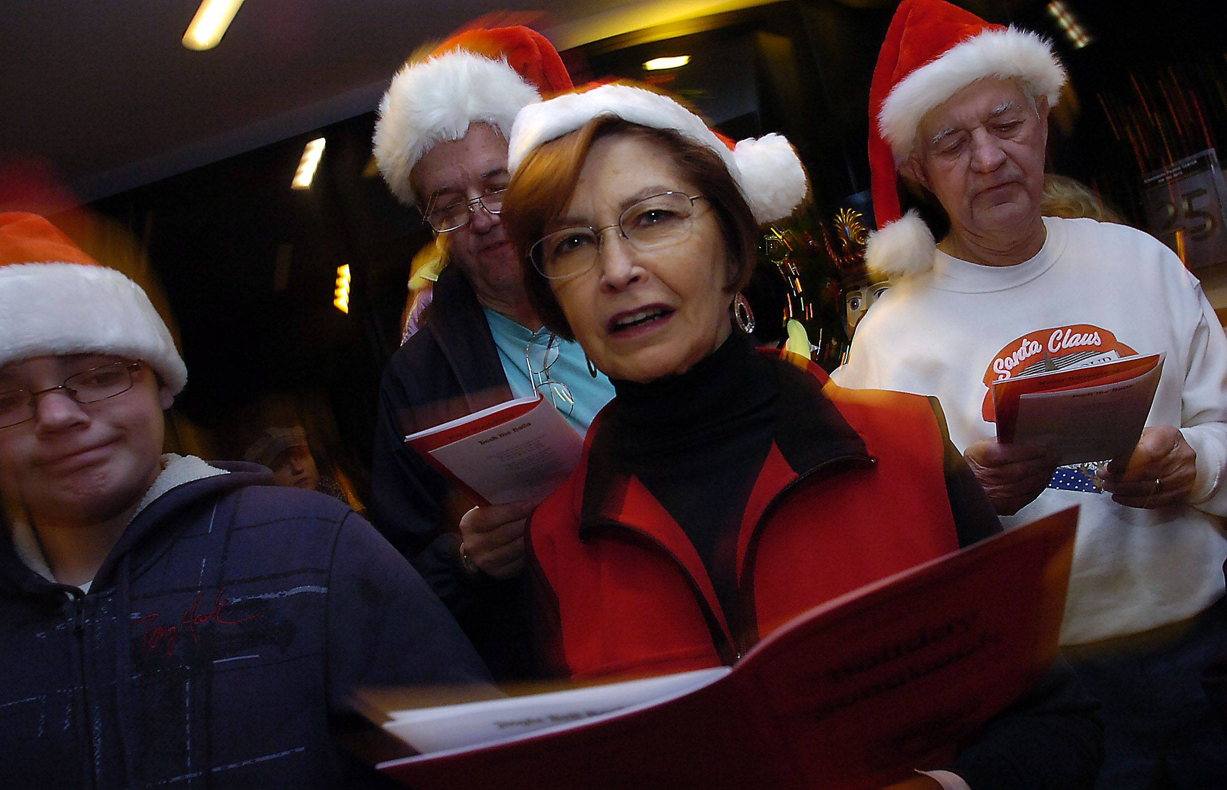 Marilyn Karr, village clerk for Schaumburg, takes part in the tree lighting ceremony singing Christmas carols in Schaumburg at the Prairie Center for the Arts on Friday.