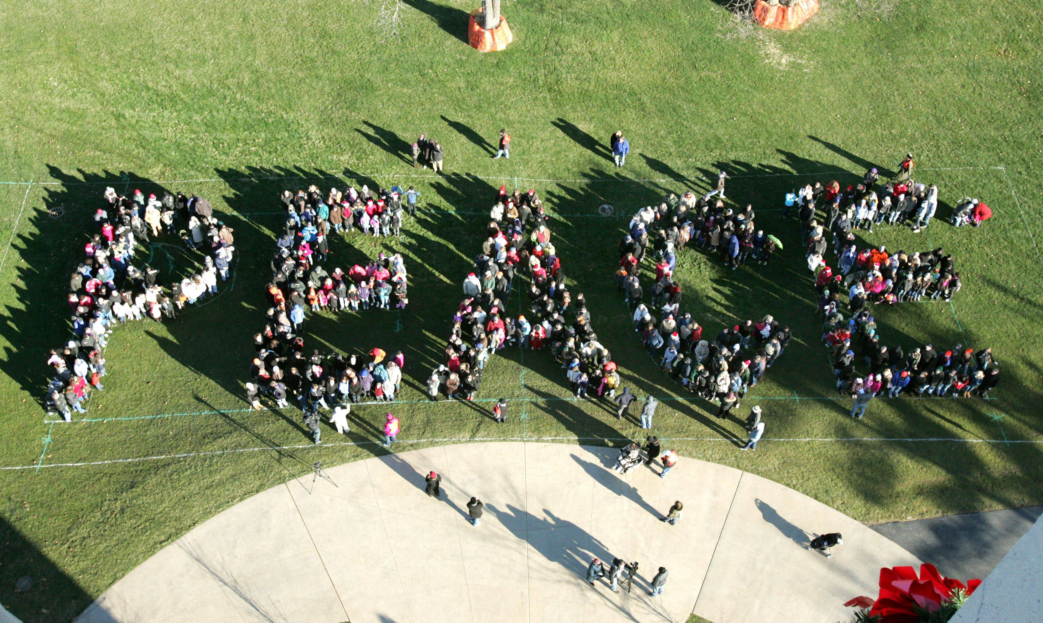 "Naperville residents participate in a community photo at Rotary Hill near the downtown Millenniumn Carillion to spell out the word ""Peace"" on Friday."