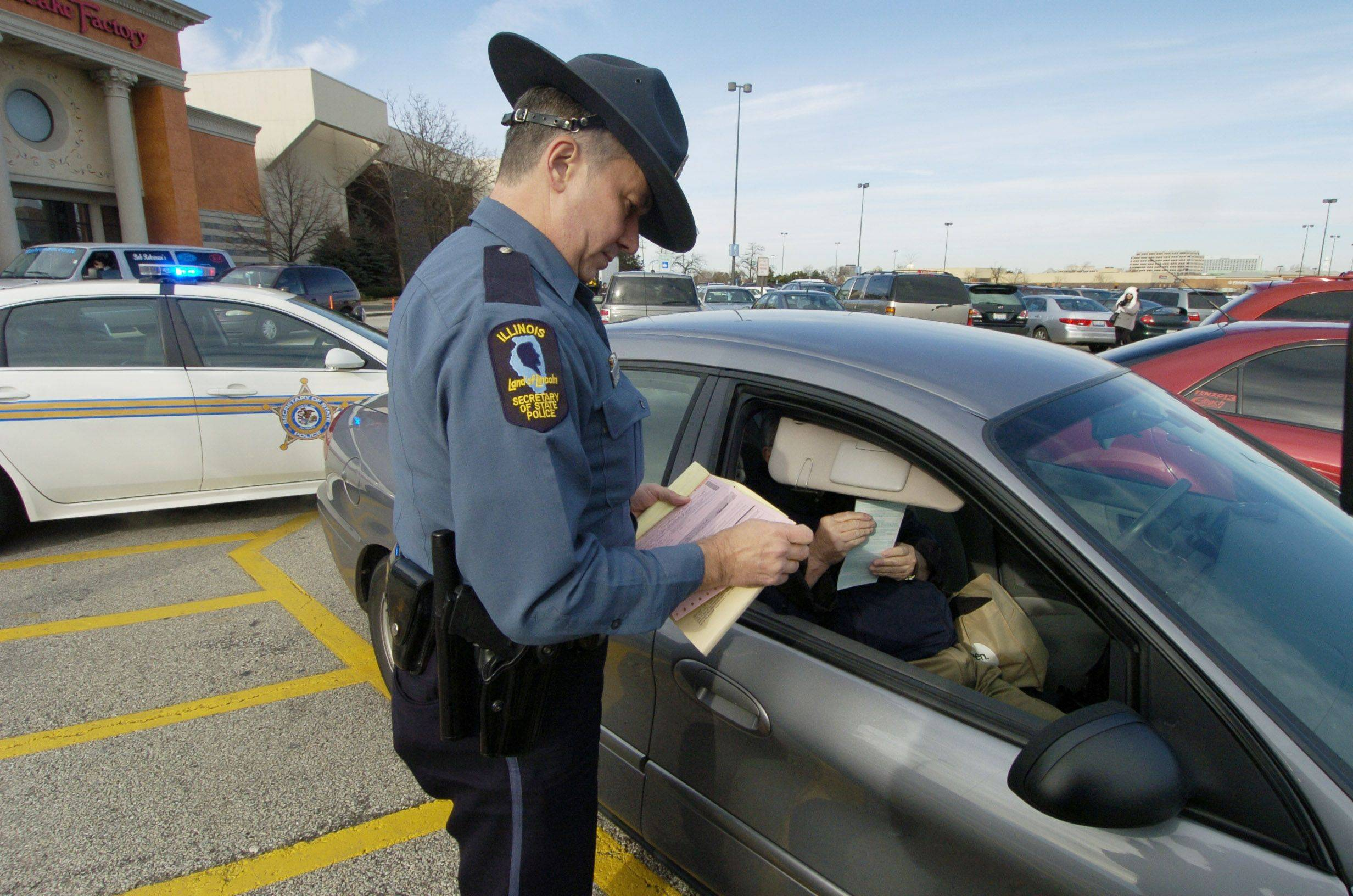 Investigator Glenn Florkow of the Illinois Secretary of State Police issues a citation to a motorist for parking improperly in a handicap space Friday outside the Woodfield mall in Schaumburg.