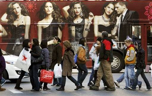 Shoppers walk in front of a tour bus with an Express clothing store ad on the side Friday in Chicago.