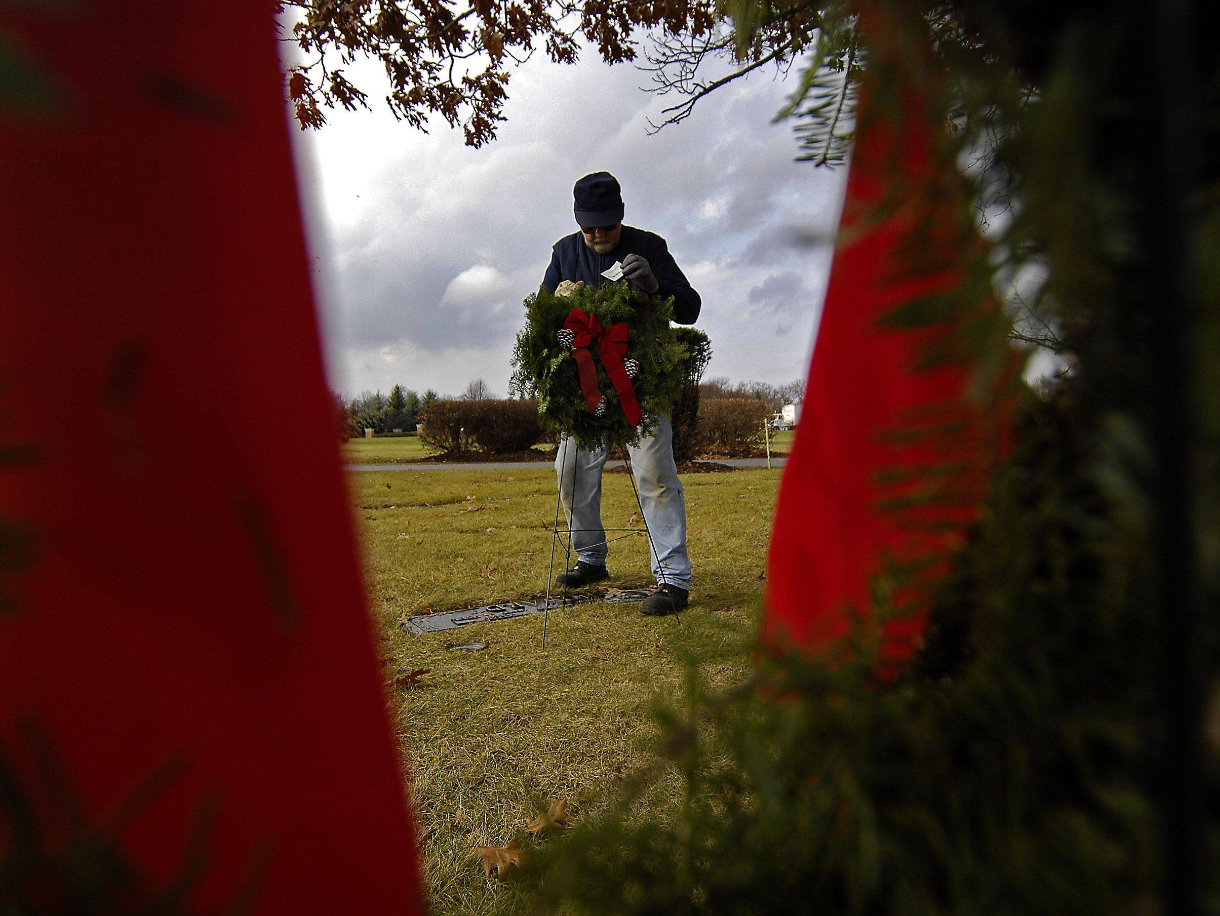 Jim Erboe places wreaths on graves at River Valley Memorial Gardens in West Dundee Monday. Erboe said he's been working in cemeteries for 52 years.