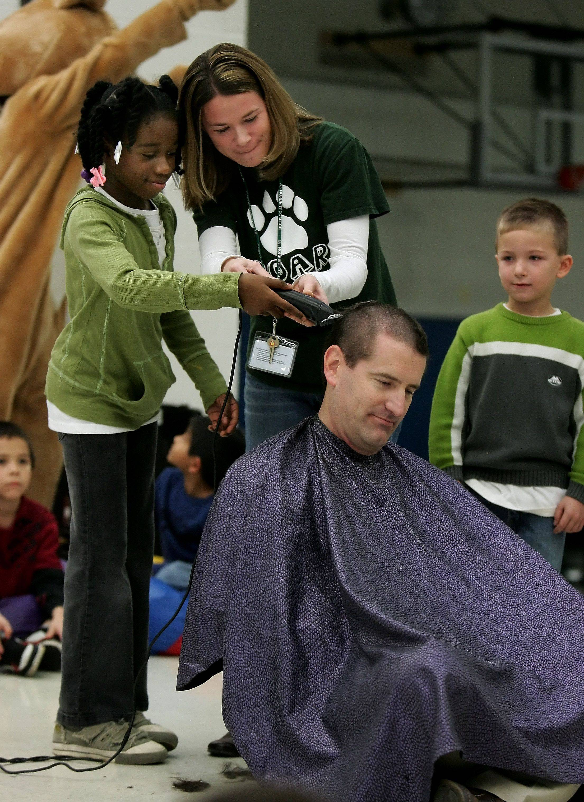 Third grader Alexia Hunter and her teacher Leah Kropp shave principal Dr. Kenneth Hyllberg's head as students from Woodland Elementary School East watch Monday during the school's Positive Interventions and Supports assembly.