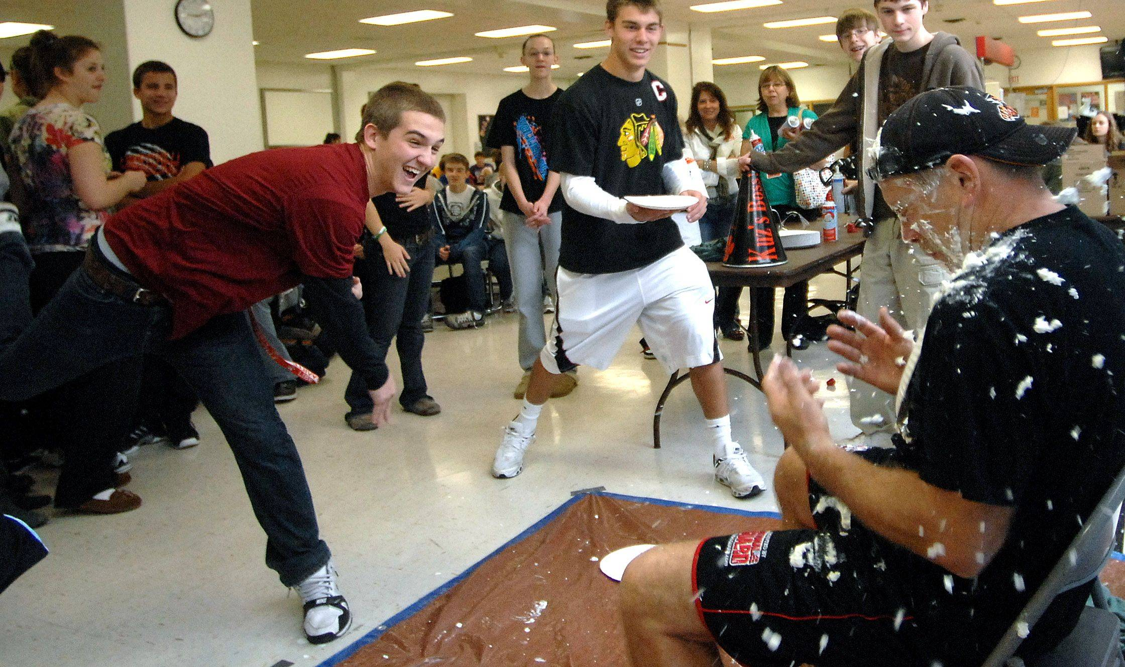 Libertyville High School senior Jake Duguid enjoys throwing a pie at head football coach Randy Kuceyeski Wednesday. Participants donated money to throw a pie, raising money for the schools Project WISH which provides Christmas presents to 183 families.